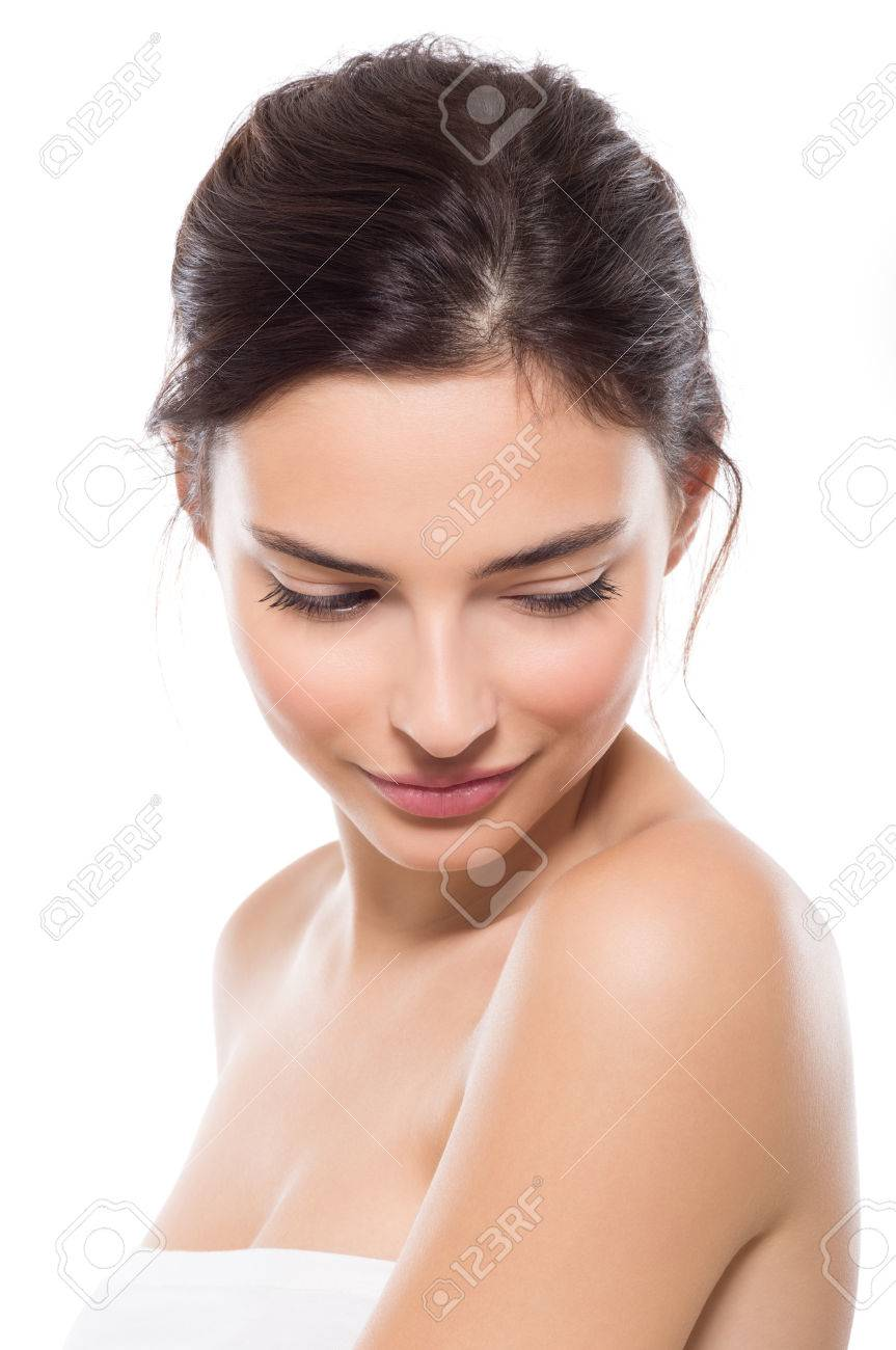 Young beautiful woman with perfect skin looking down. Close up face of beauty young woman. Young beautiful woman feeling shy isolated on white background. Wellness and skin care concept. - 65157777