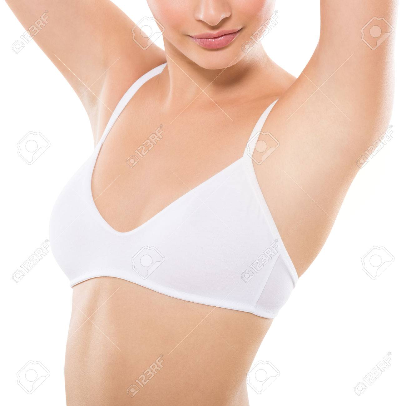 Closeup of a beautiful young woman showing her smooth armpit isolated on white background. Girl holding her arms up and showing clean underarms. Hairs removal and depilation concept. Banque d'images - 65157778