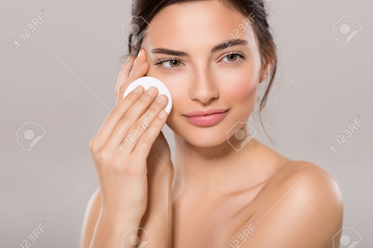 Healthy fresh girl removing makeup from her face with cotton pad. Beauty woman cleaning her face with cotton swab pad isolated on grey background. Skin care and beauty concept. Banque d'images - 65157888