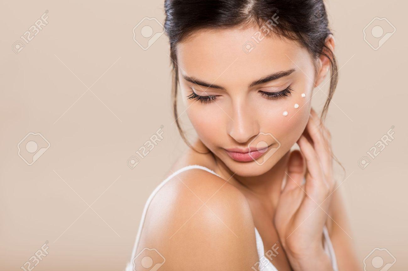 Jeune femme regardant vers le bas avec le visage hydratant à proximité des yeux. Belle femme appliquant lotion pour le visage sur sa joue. Belle intime fille brune avec un sentiment parfait et une peau saine timide isolé sur fond chaud. Banque d'images - 65157893