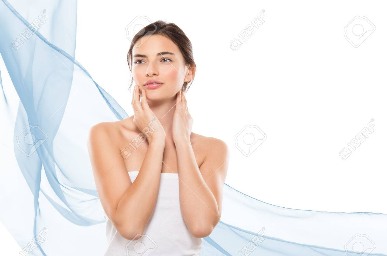 Young woman looking away while touching her face isolated on white background. Beauty brunette girl feeling fresh after spa treatment with copy space on right side and blue waves of cloths. Beauty and skincare therapy. Banque d'images - 65157925
