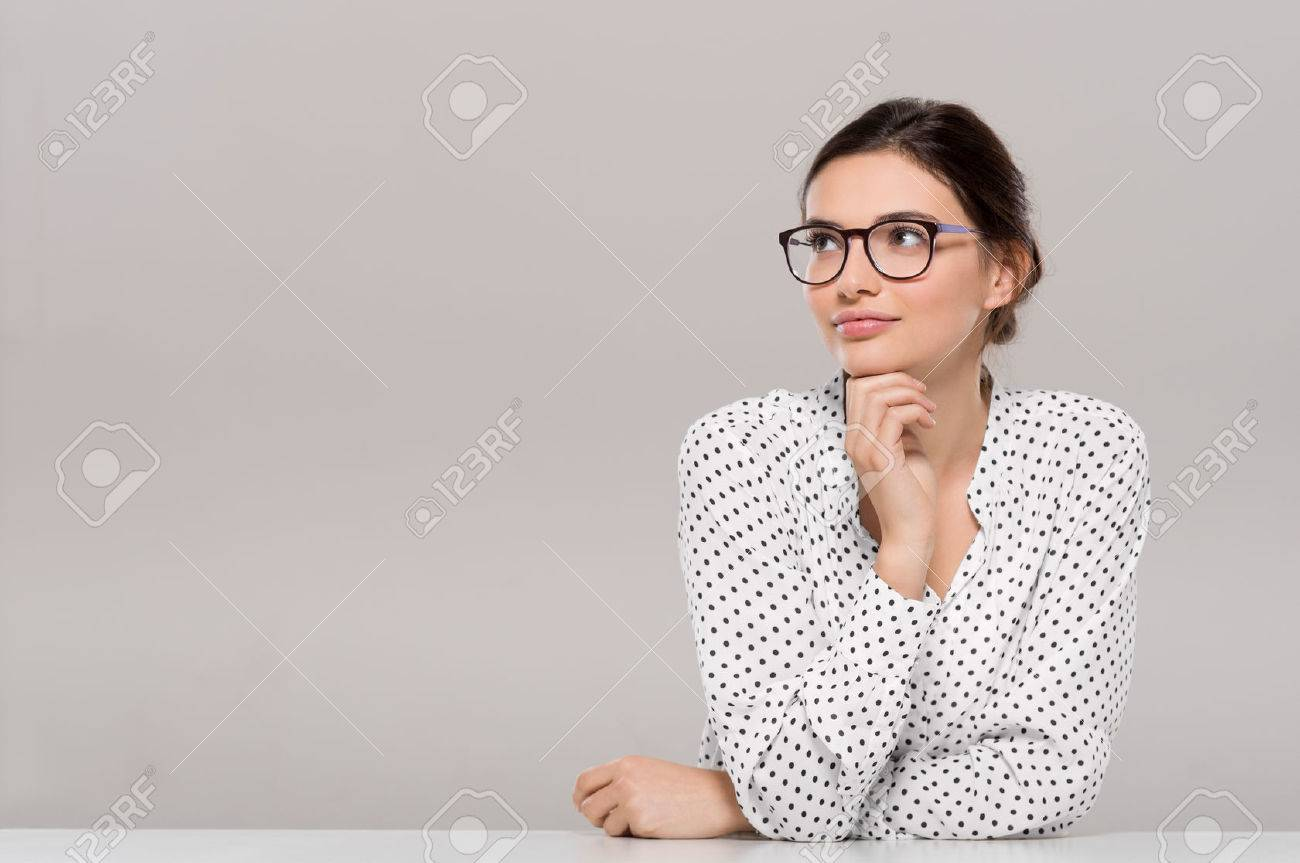 Beautiful young businesswoman wearing glasses and thinking with hand on chin. Smiling pensive woman with eyeglasses looking away isolated on grey background. Fashion and contemplative girl smiling and meditating on project. Banque d'images - 65158037