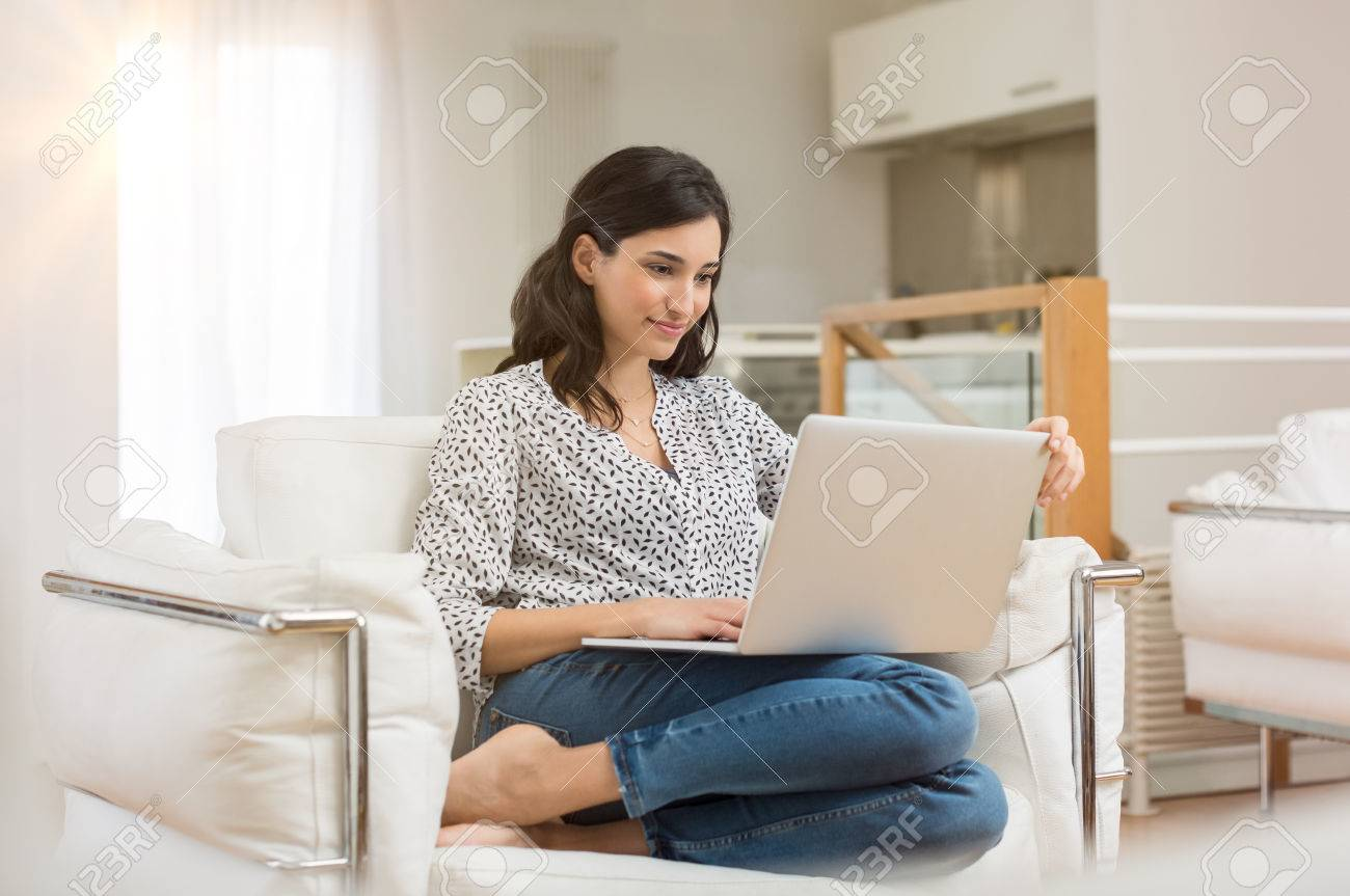 Young woman doing research work for her business. Smiling woman sitting on sofa relaxing while browsing online shopping website. Happy girl browsing through the internet during free time at home. Banque d'images - 70750599