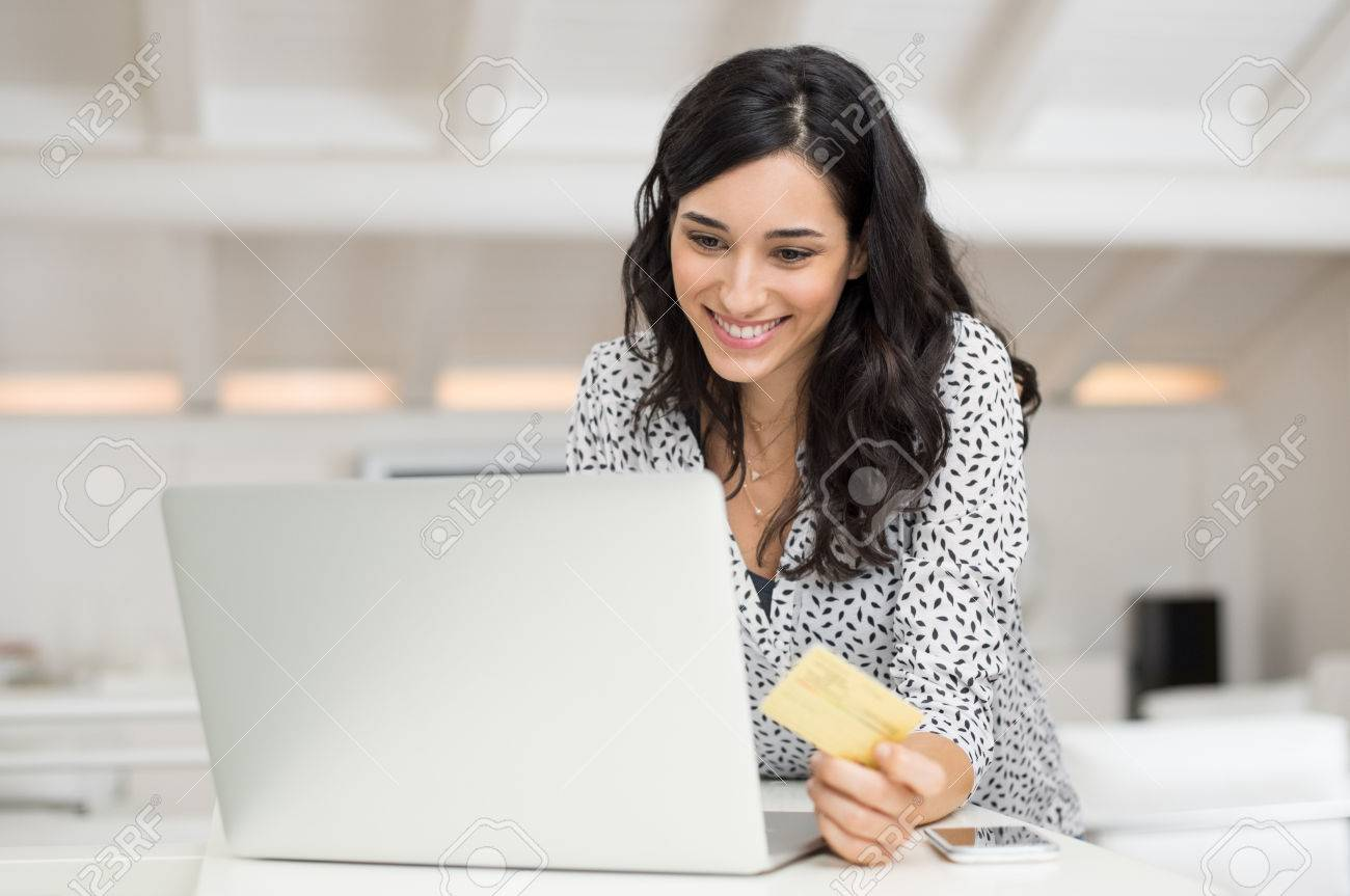 Happy young woman holding a credit card and shopping online at home. Beautiful girl using laptop to shop online with creditcard. Smiling woman using laptop and credit card for online payment. - 71465178