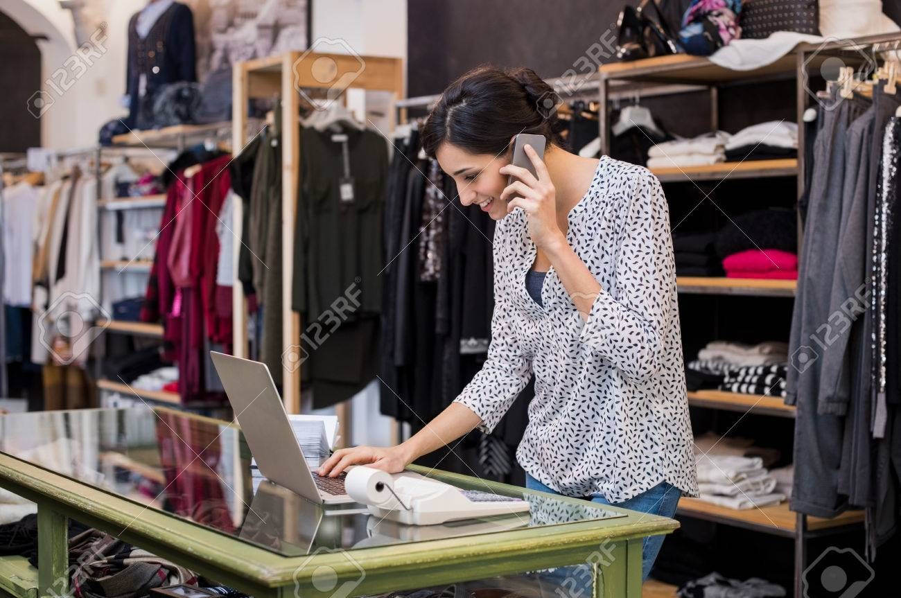 Young businesswoman talking over phone while checking laptop in her clothing store. Young entrepreneur in casual using laptop and talking on mobile. Store manager woman checking important documents on laptop. Small business concept. Banque d'images - 69226668