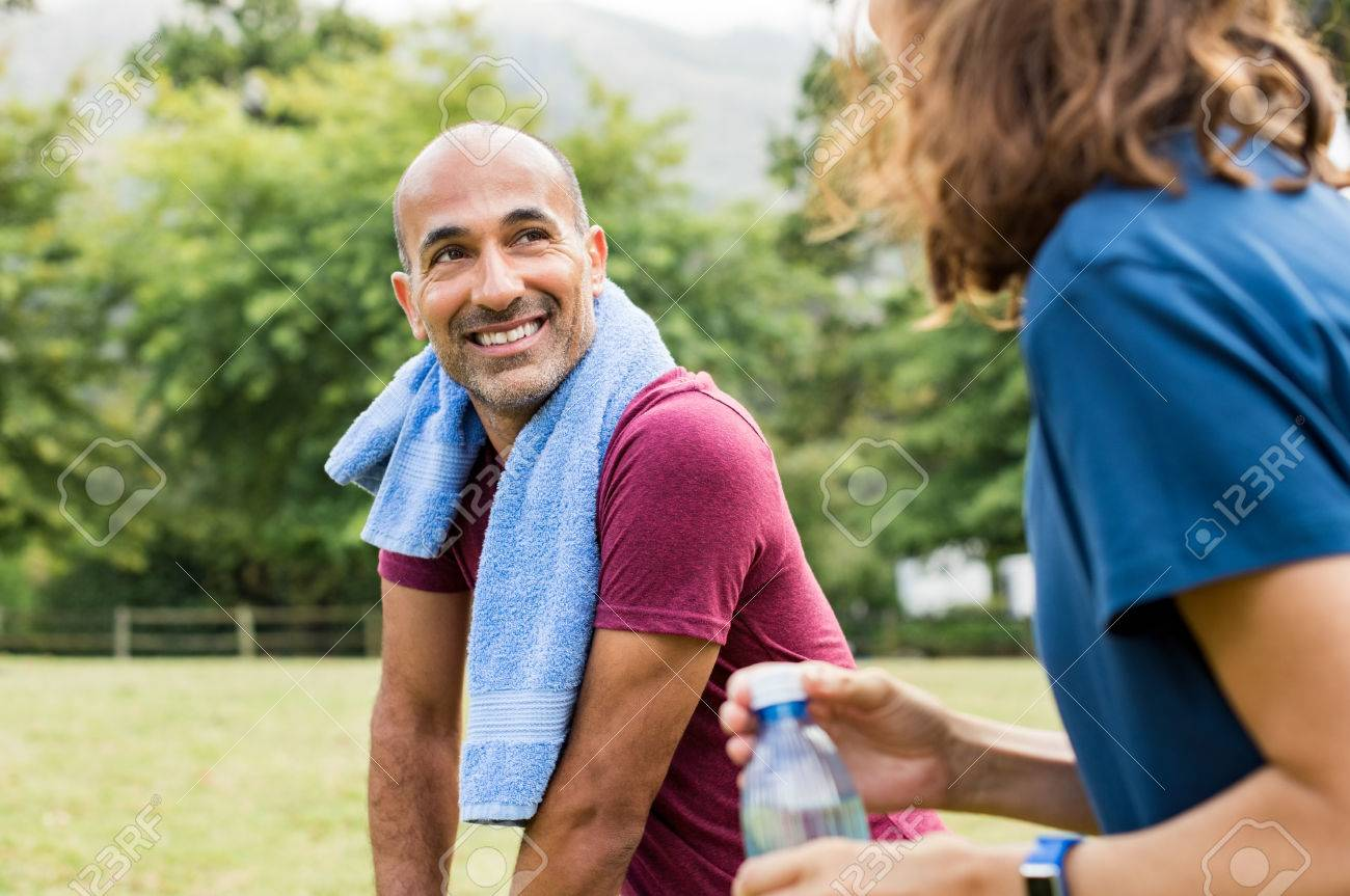 mature man with towel around neck talking to mid woman outdoor after