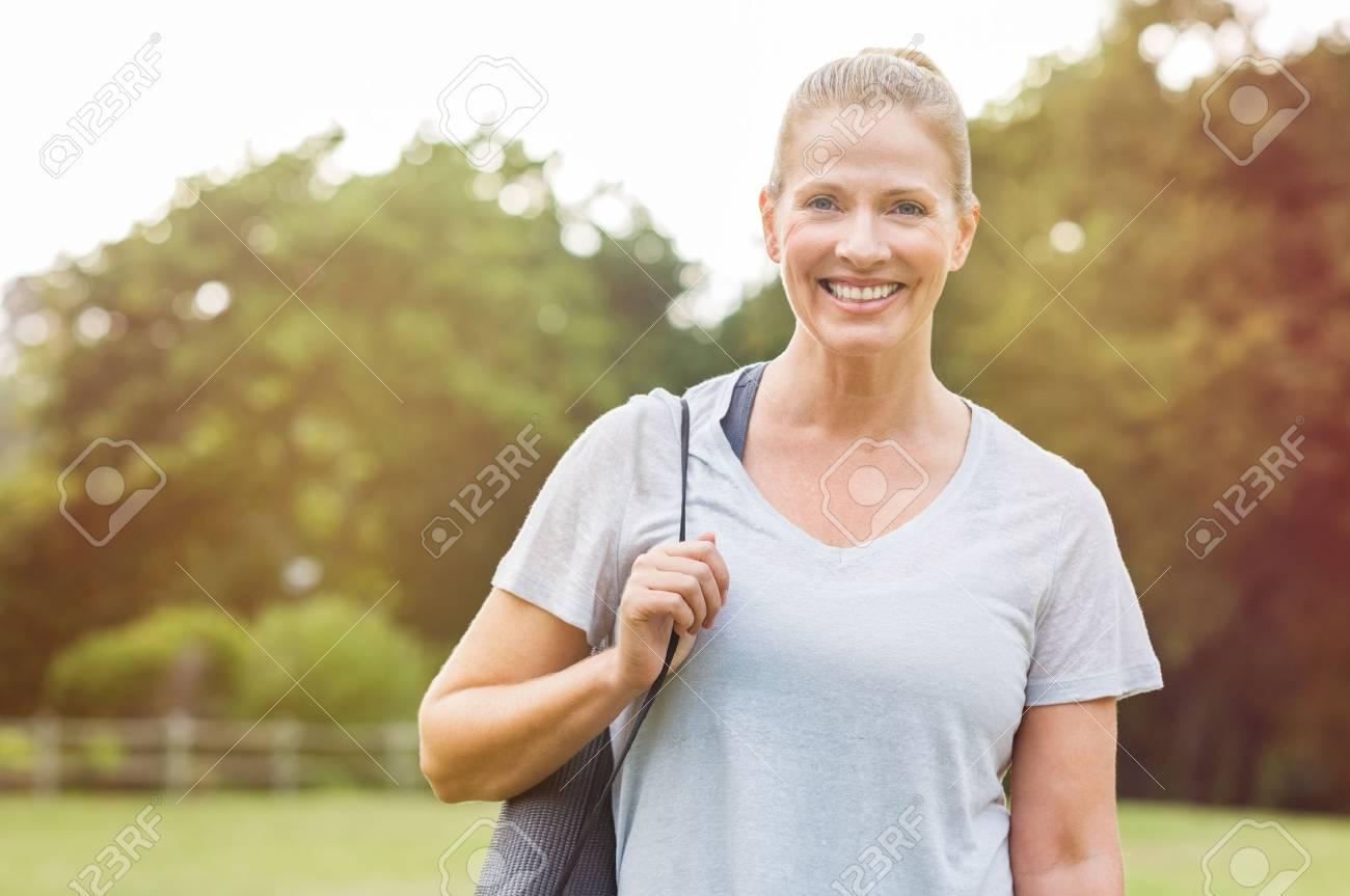 senior schöne frau mit einem grauen yoga-matte für die ausübung der  vorbereitung zu halten. porträt einer reifen frau lächelnd mit  fitness-matte im