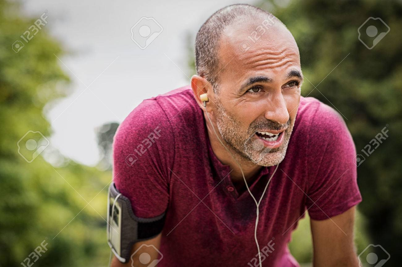Portrait of athletic mature man after run. Handsome senior man resting after jog at the park on a sunny day. Sweaty multiethnic man listening to music while jogging. Banque d'images - 75431205