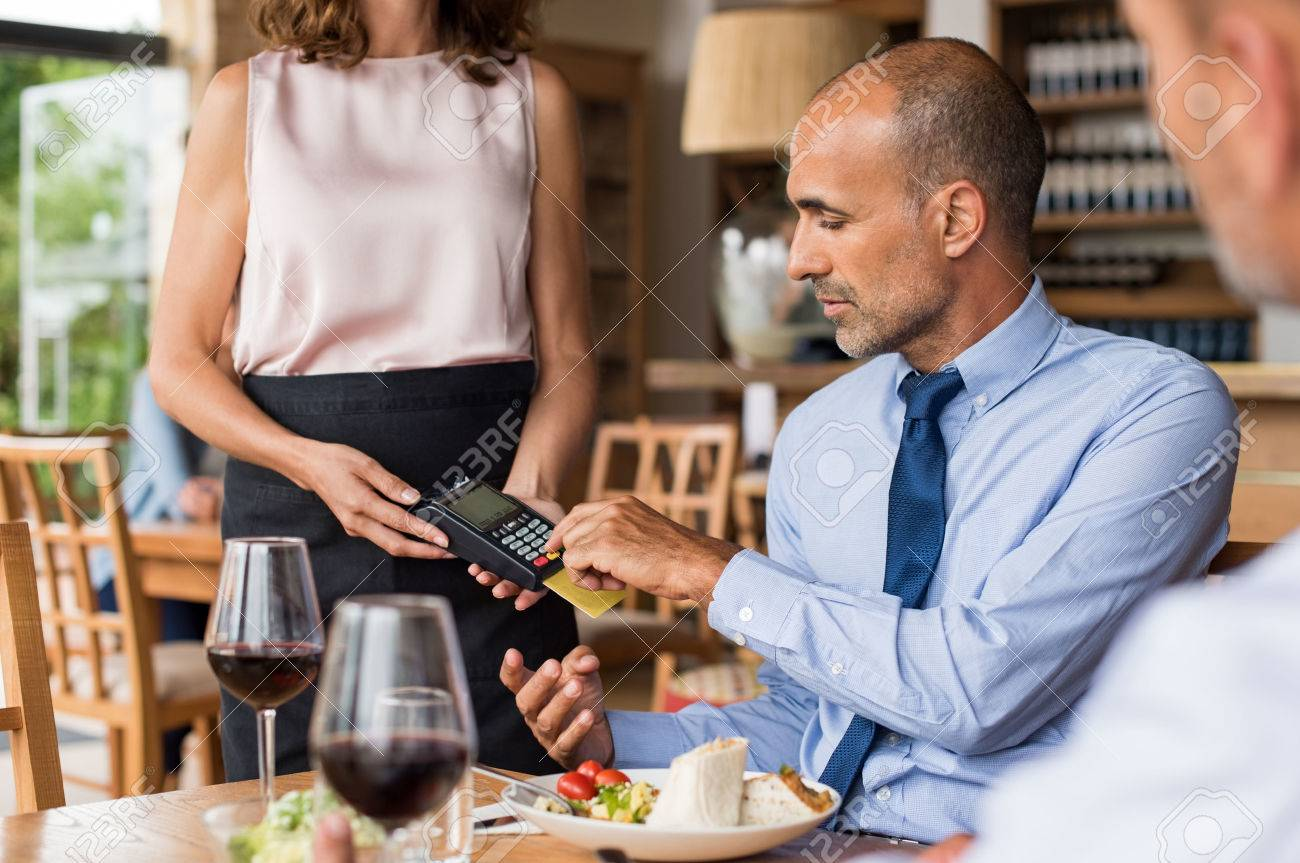 Waiter holding credit card swipe machine while customer typing code. Mature businessman making payment in cafe through credit card. Customer paying bill of lunch with debit card. - 75298833