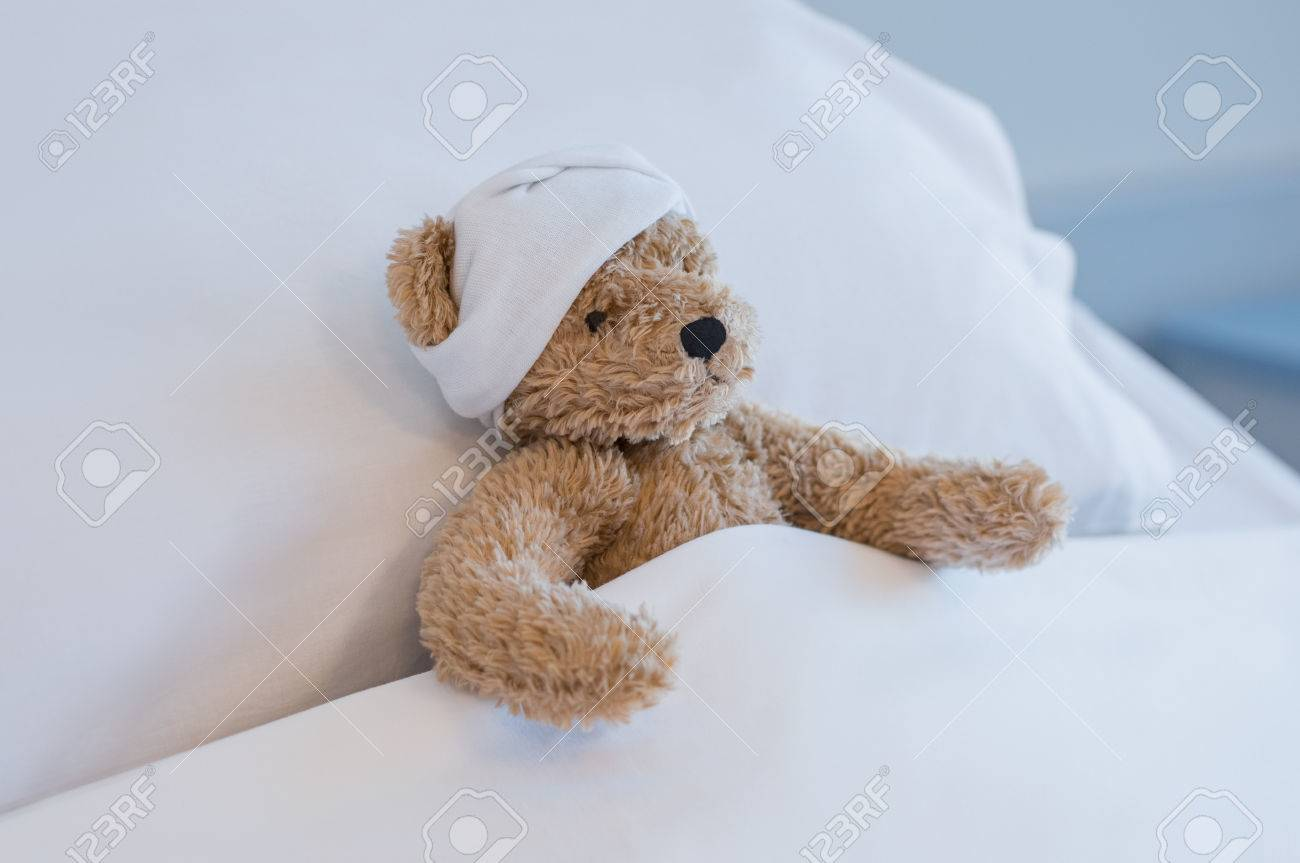 Injured teddy bear sleeping on hospital bed. Brown plush toy with a headache resting on bed. Sick brown bear with a bandage on his head lying in bed hospitalized at medical clinic. Banque d'images - 76464103