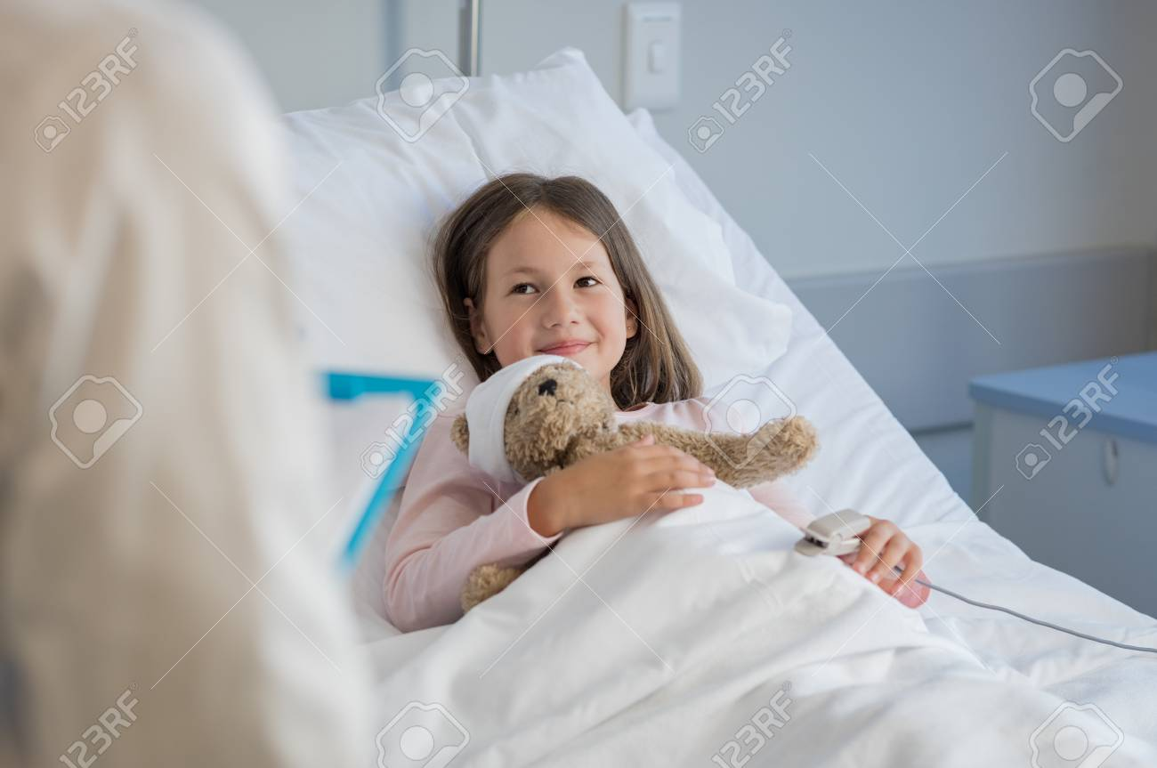 Smiling Little Girl With Oxygen Saturated Probe Resting On Hospital ...