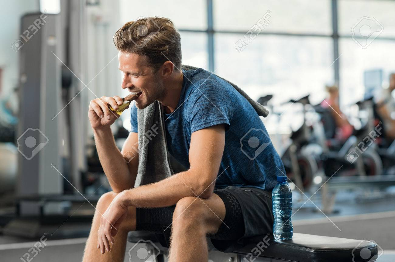 Sweaty young man eating energy bar at gym. Handsome mid guy enjoying chocolate after a heavy workout in fitness studio. Fit man biting a snack and resting on bench. - 78131605