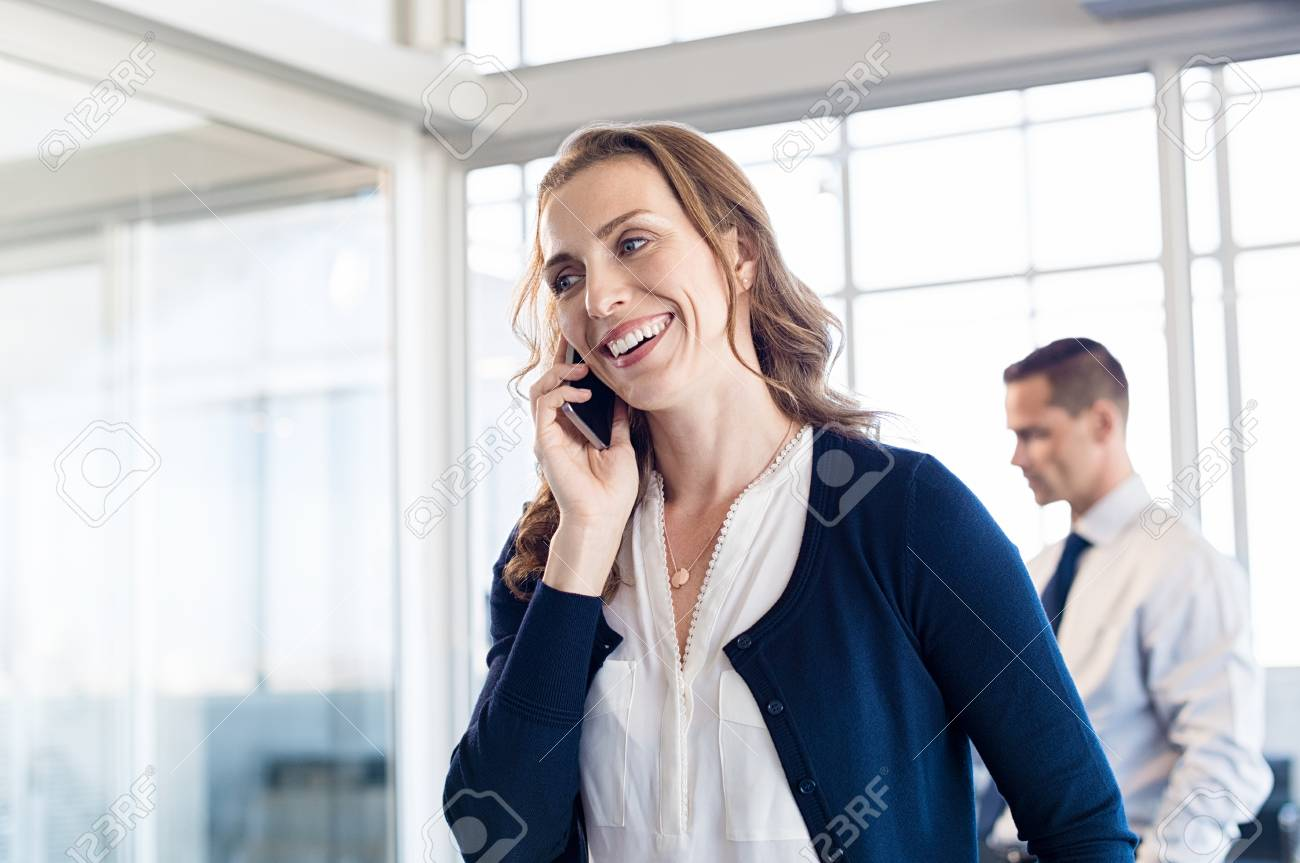 Mature Business Woman Talking Over Phone In Boardroom Happy