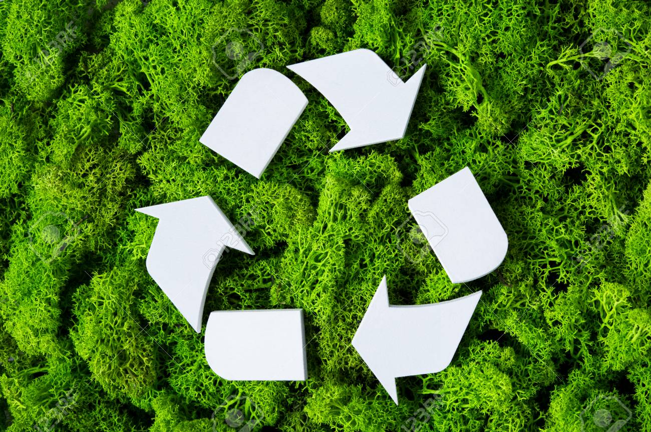 Top view of white recycle eco symbol on green moss with copy space. High angle view of recycled sign and eco concept on green background. Recycling and conservation of the environment sign. - 88026258