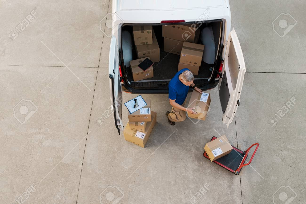 Delivery man holding cardboard box and unloading parcel for delivery. Top view of courier unloading parcels from van. High angle view of man removing packages for the delivery. - 92686616