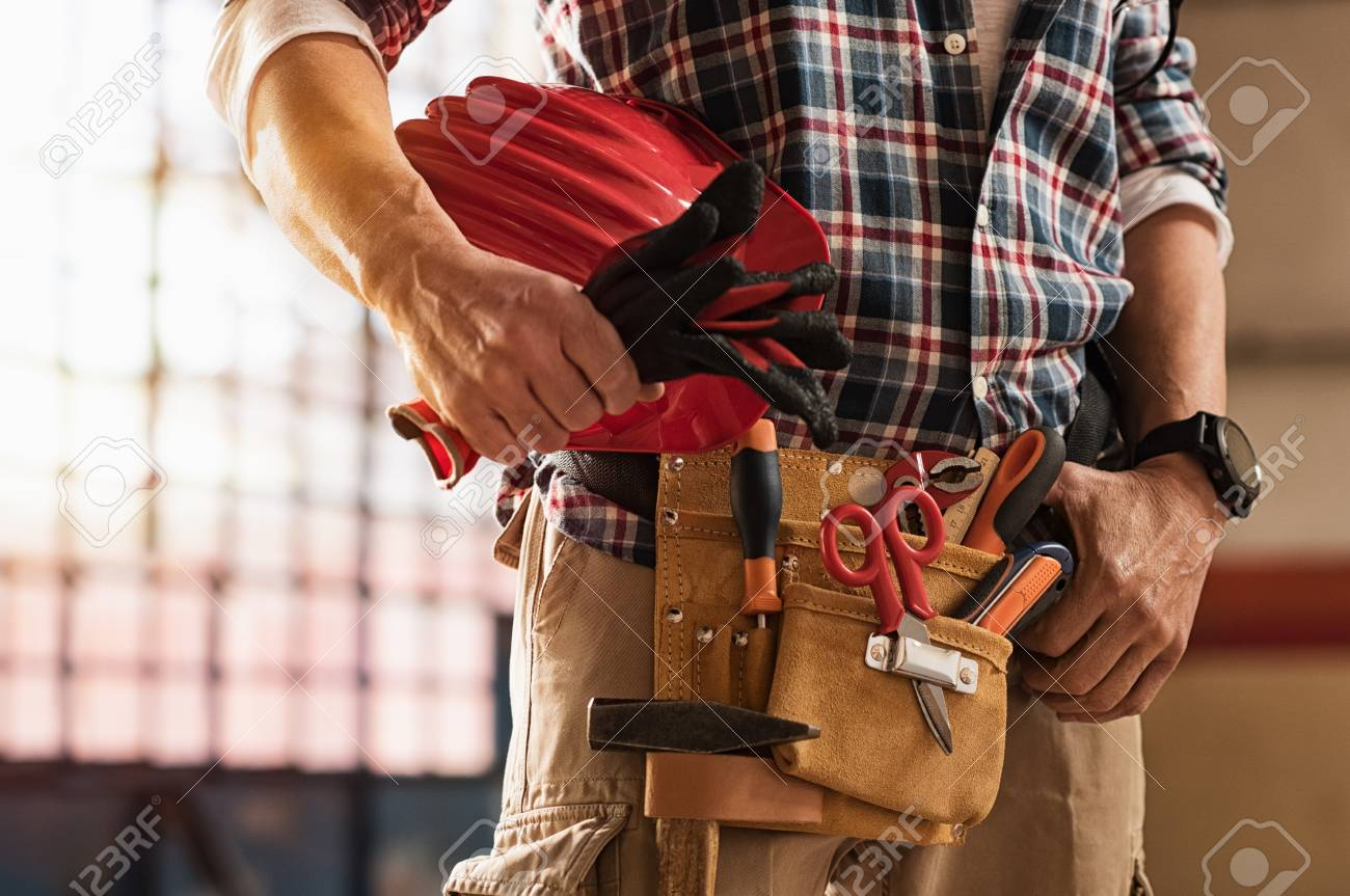 Closeup of bricklayer hands holding hardhat and construction equipment. Detail of mason man hands holding work gloves and wearing tool kit on waist. Handyman with tools belt and artisan equipment. - 92679167