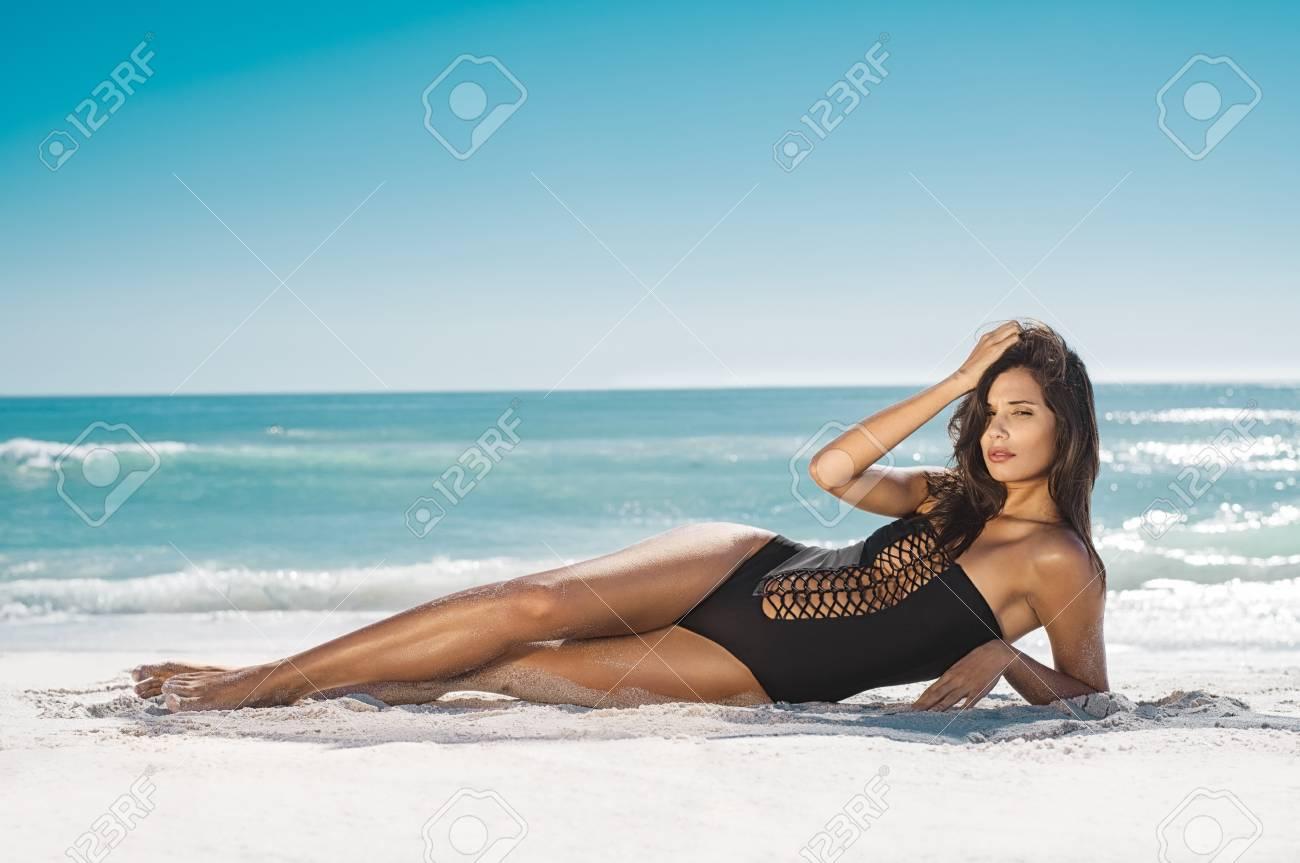Fashion woman in black swimwear lying on tropical beach. Portrait of beautiful young woman lying on side enjoying sunbath near the sea shore. Sexy tanned girl in stylish swimsuit looking at camera. - 97630723