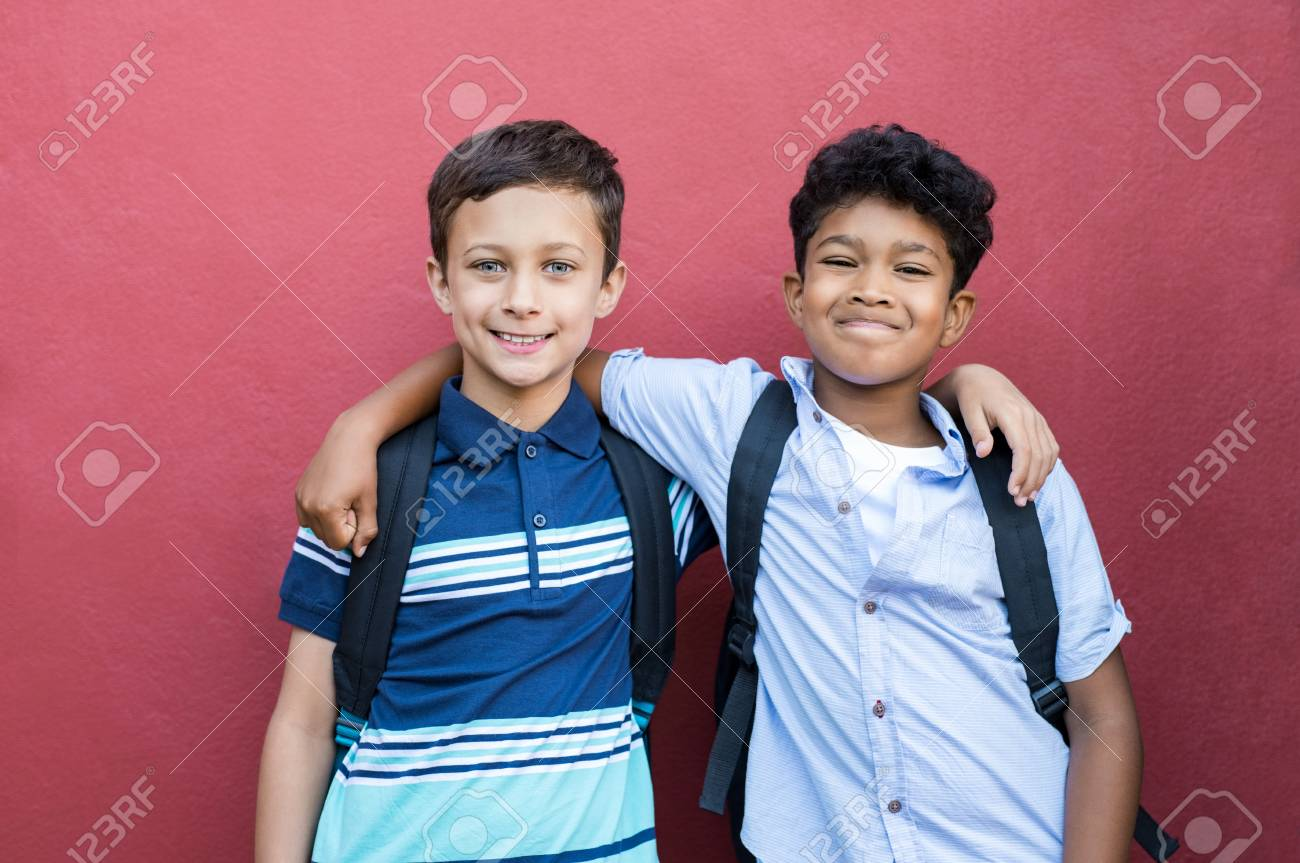 Best children friends standing with hand on shoulder against red background happy smiling classmates standing