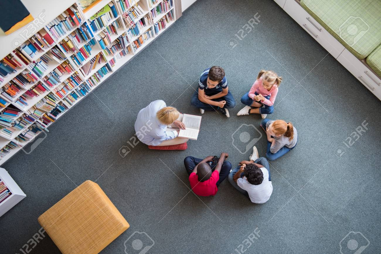 Teacher reading fairy tales to children sitting in a circle at library. Top view of librarian sitting with five multiethnic children on floor. Teacher reading book to cute girls and young boys at school. - 100140682