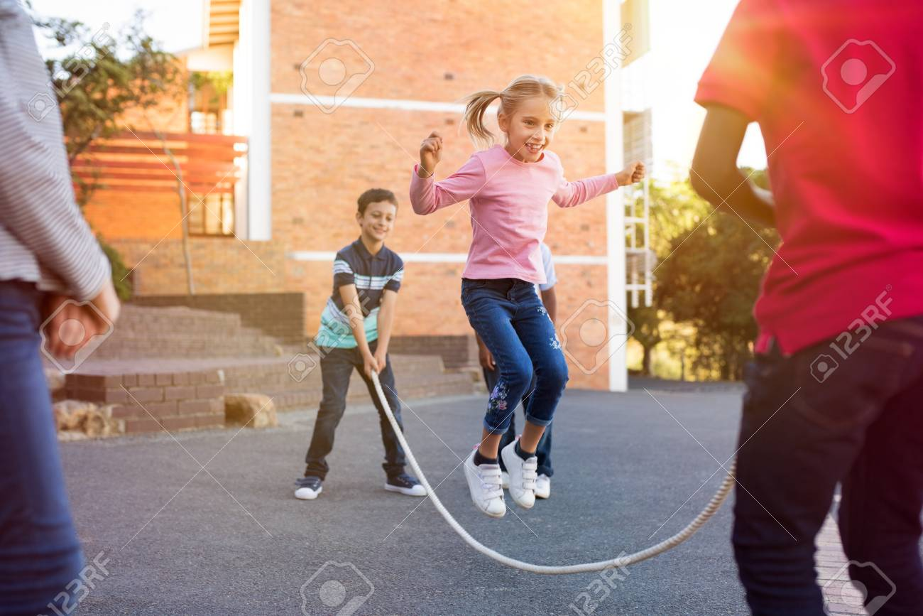 Happy elementary kids playing together with jumping rope outdoor. Children playing skipping rope jumping game and laughing outdoors. Happy cute girl jumping over skipping rope held by her friends. - 103854843