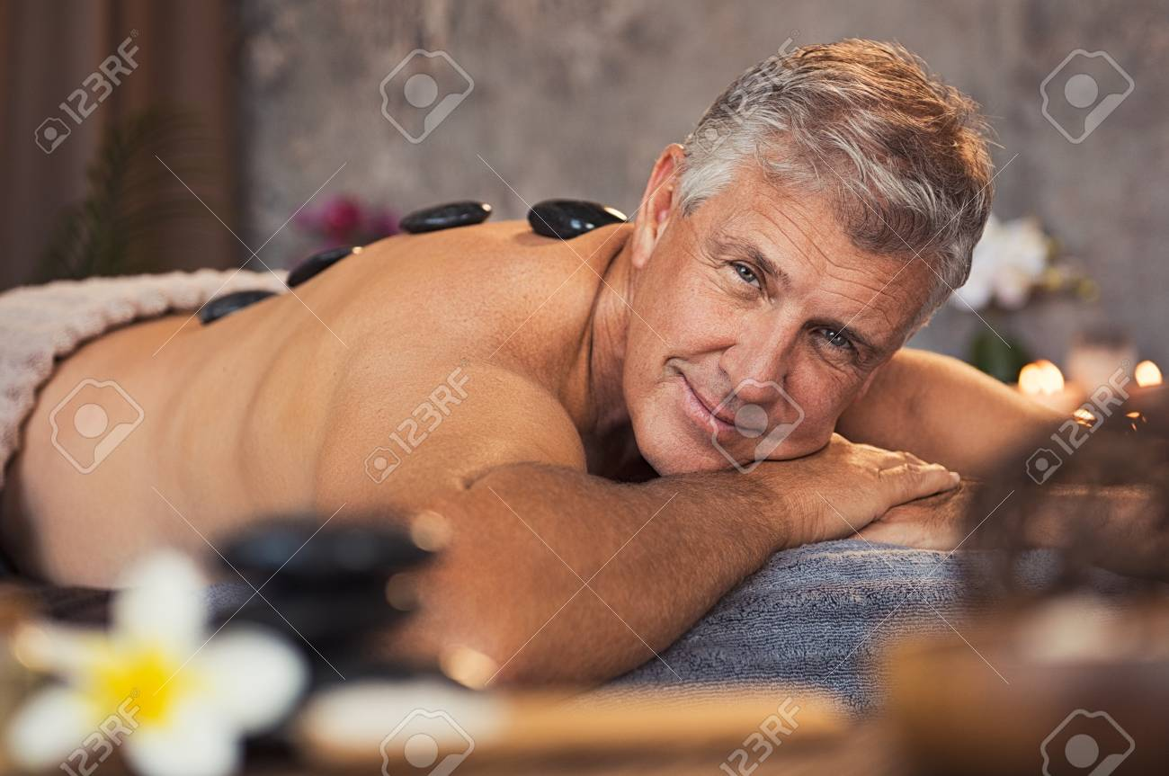 Smiling mature man pampering himself at spa with body treatment. Man with  grey hair lying naked and relaxing during hot stone massage.