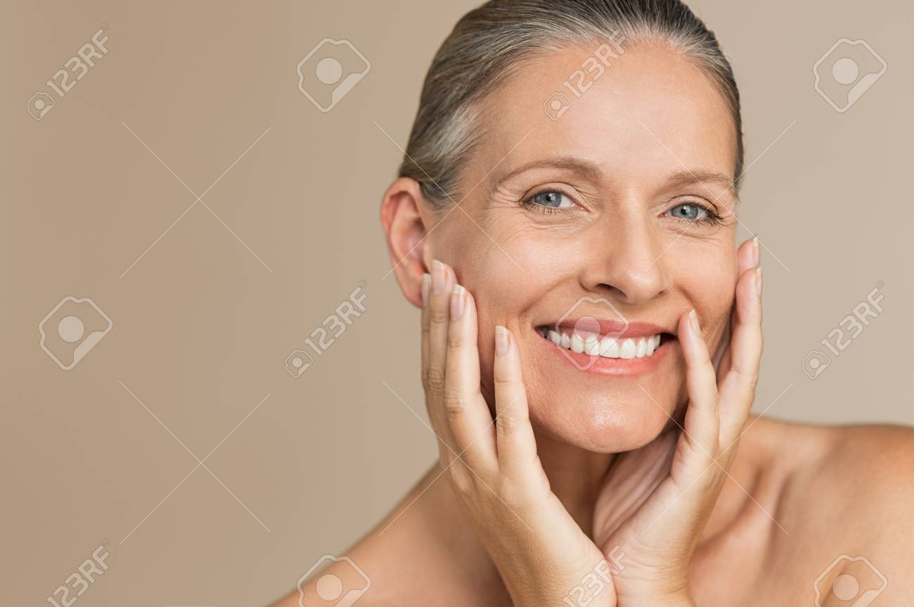 Beauty portrait of mature woman smiling with hand on face. Closeup face of happy senior woman feeling fresh after anti-aging treatment. Smiling beauty looking at camera while touching her perfect skin. - 104902226