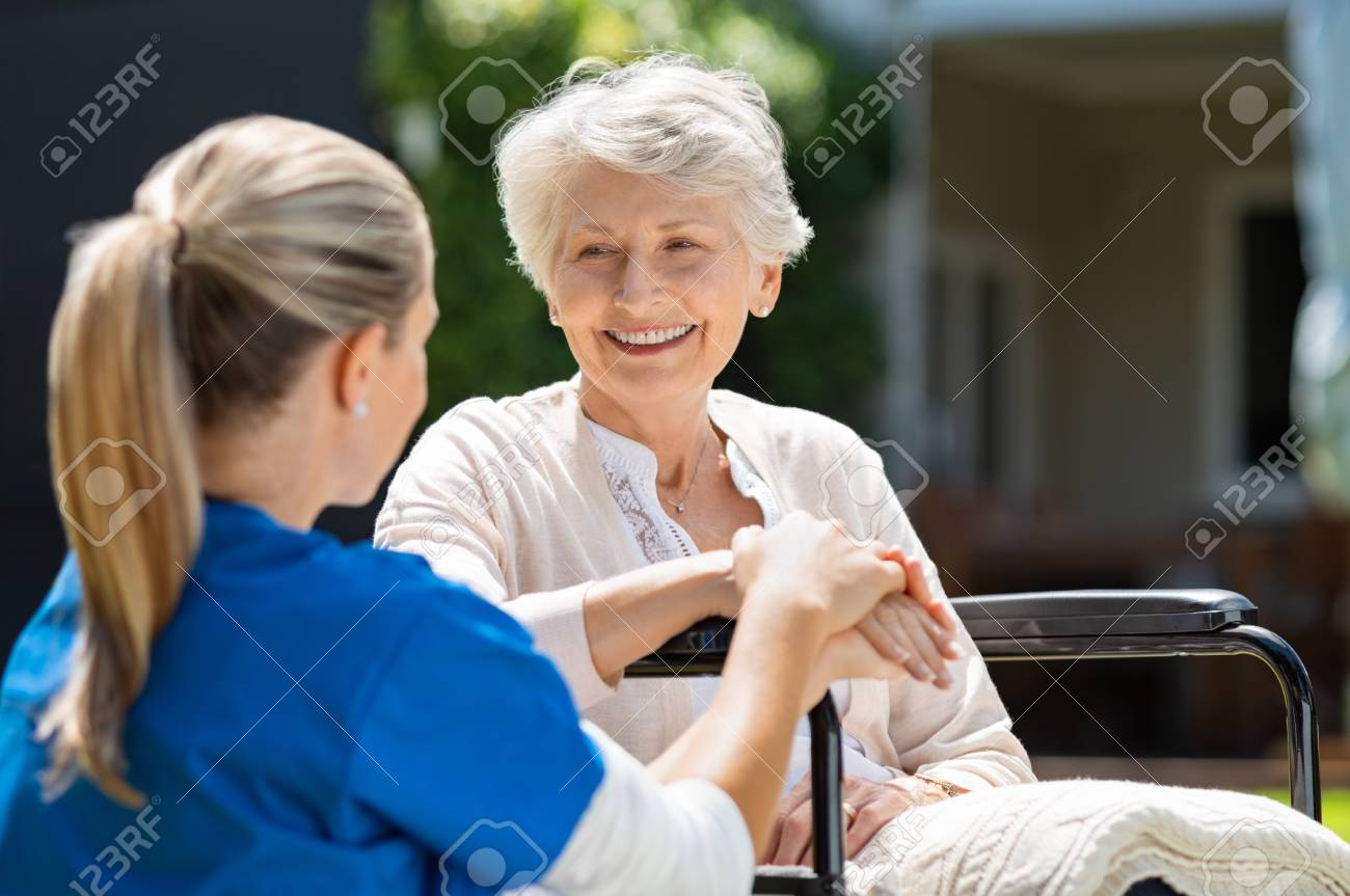 Smiling senior patient sitting on wheelchair with nurse supporting her. Doctor looking at elderly patient on a wheelchair in the garden. Nurse holding hand of mature woman outside pension home. - 107595457