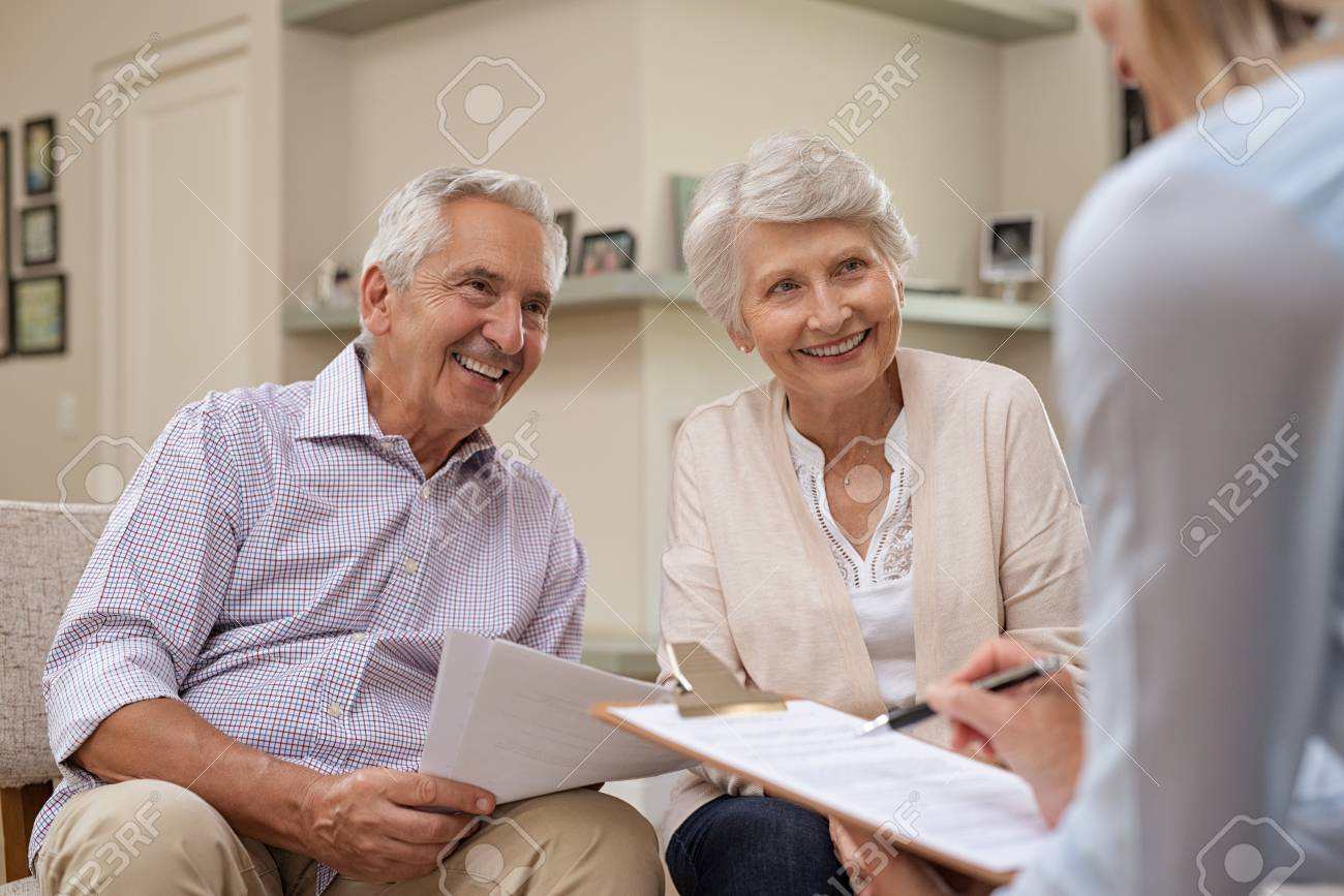 Senior couple meeting real estate agent at home. Old husband and wife with financial advisor for investment opportunities. Happy elderly man and woman listening to various investment plans for their retirement. - 107595473