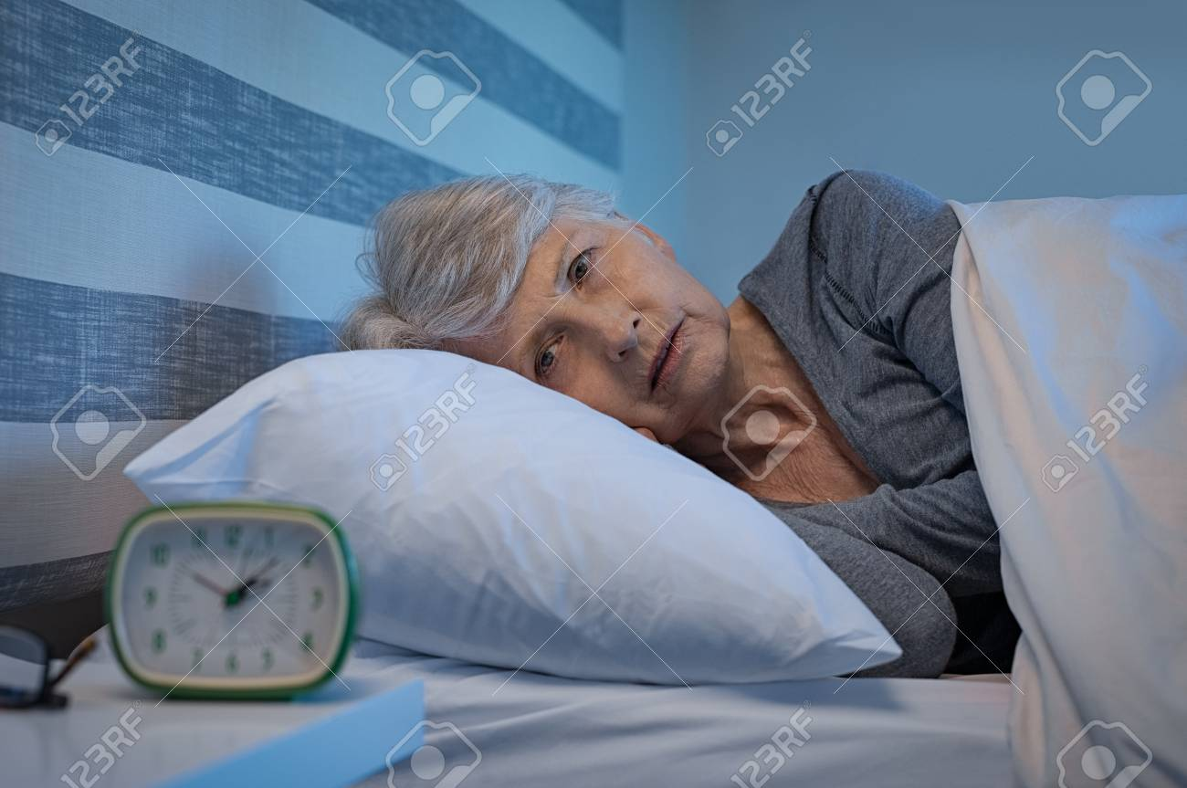 Worried senior woman in bed at night suffering from insomnia. Old woman lying in bed with open eyes. Mature woman unable to sleep at home. - 107596025