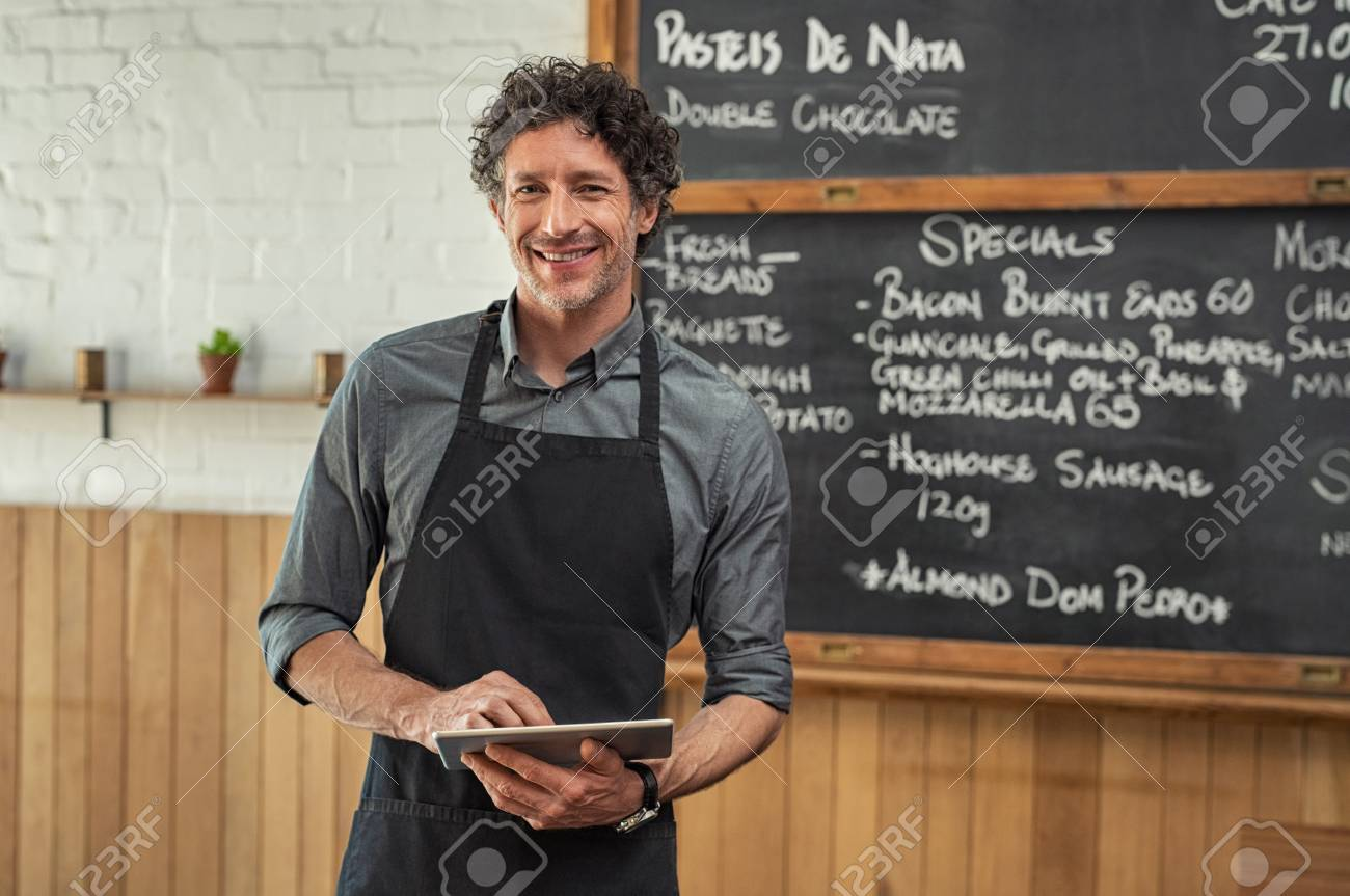 Mature waiter wearing black apron and standing in front of the blackboard with the menu of the day. Portrait of smiling man holding digital tablet and looking at camera. Happy small business owner working in cafeteria with digital tablet. - 108467983