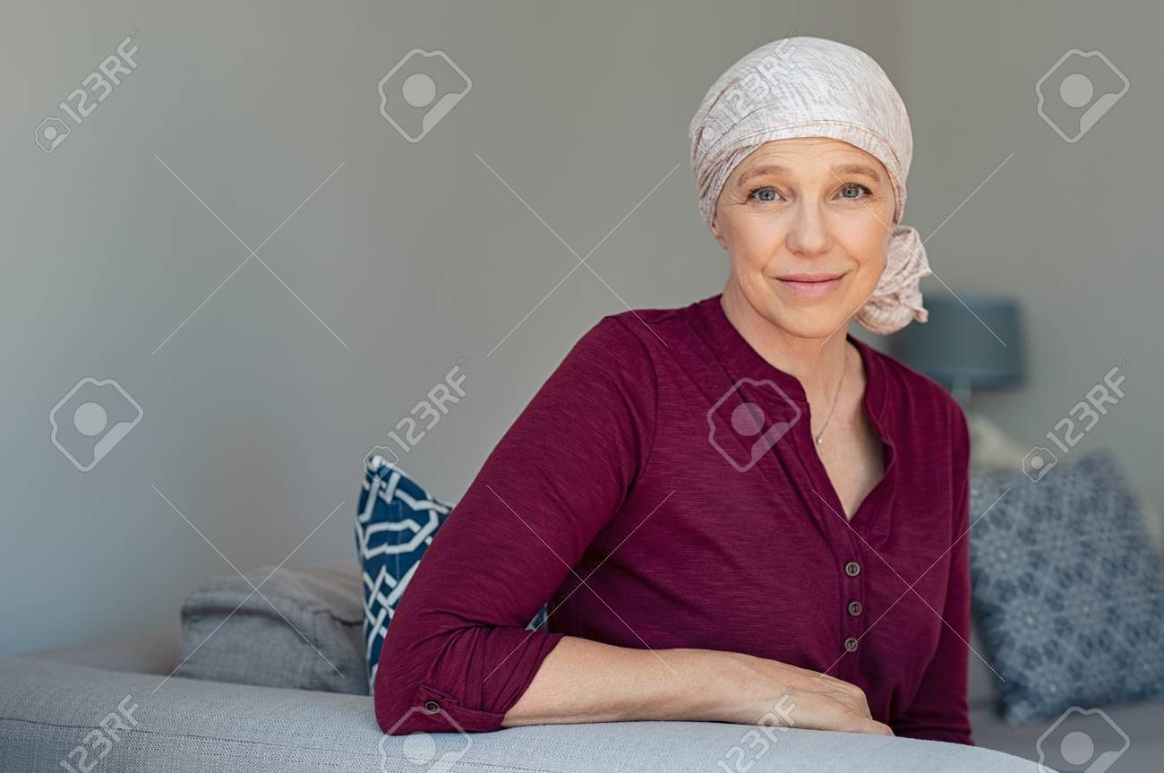Mature woman with cancer in pink headscarf smiling sitting on couch at home. - 108885129