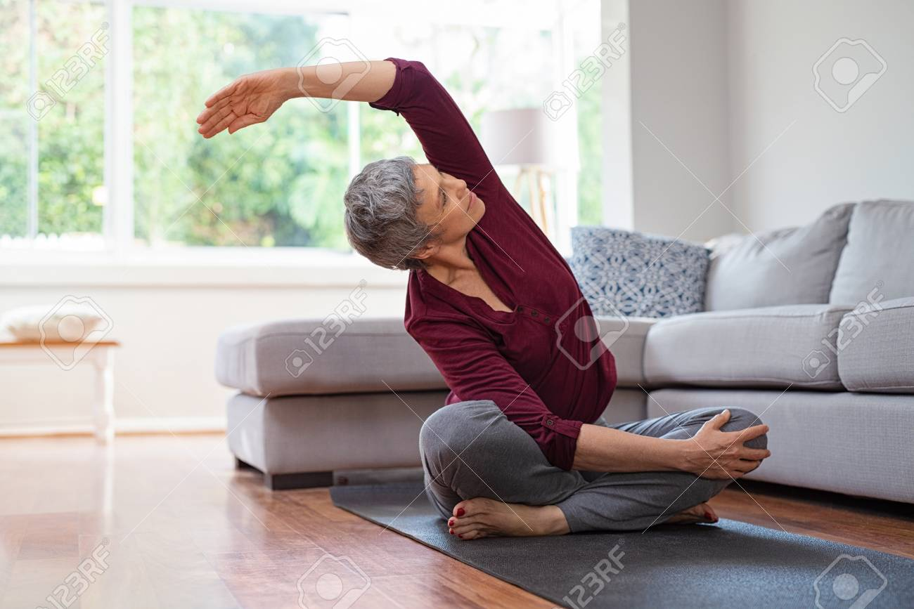 Senior woman exercising while sitting in lotus position. Active mature woman doing stretching exercise in living room at home. Fit lady stretching arms and back while sitting on yoga mat. - 108885137