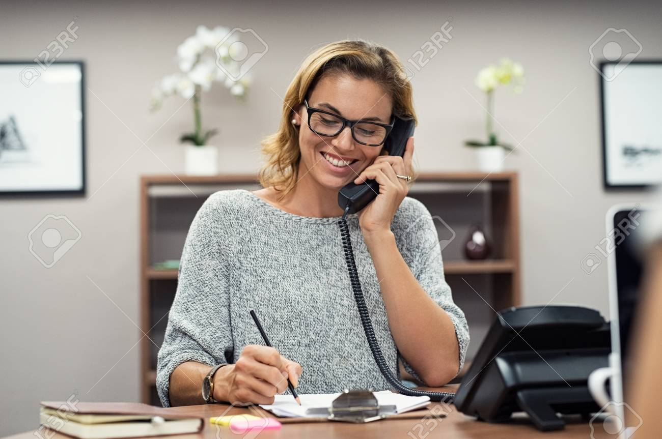 Beautiful mature woman talking on phone at creative office. Happy smiling businesswoman answering telephone at office desk. Casual business woman sitting at her desk making telephone call and taking notes on notebook. - 113992595