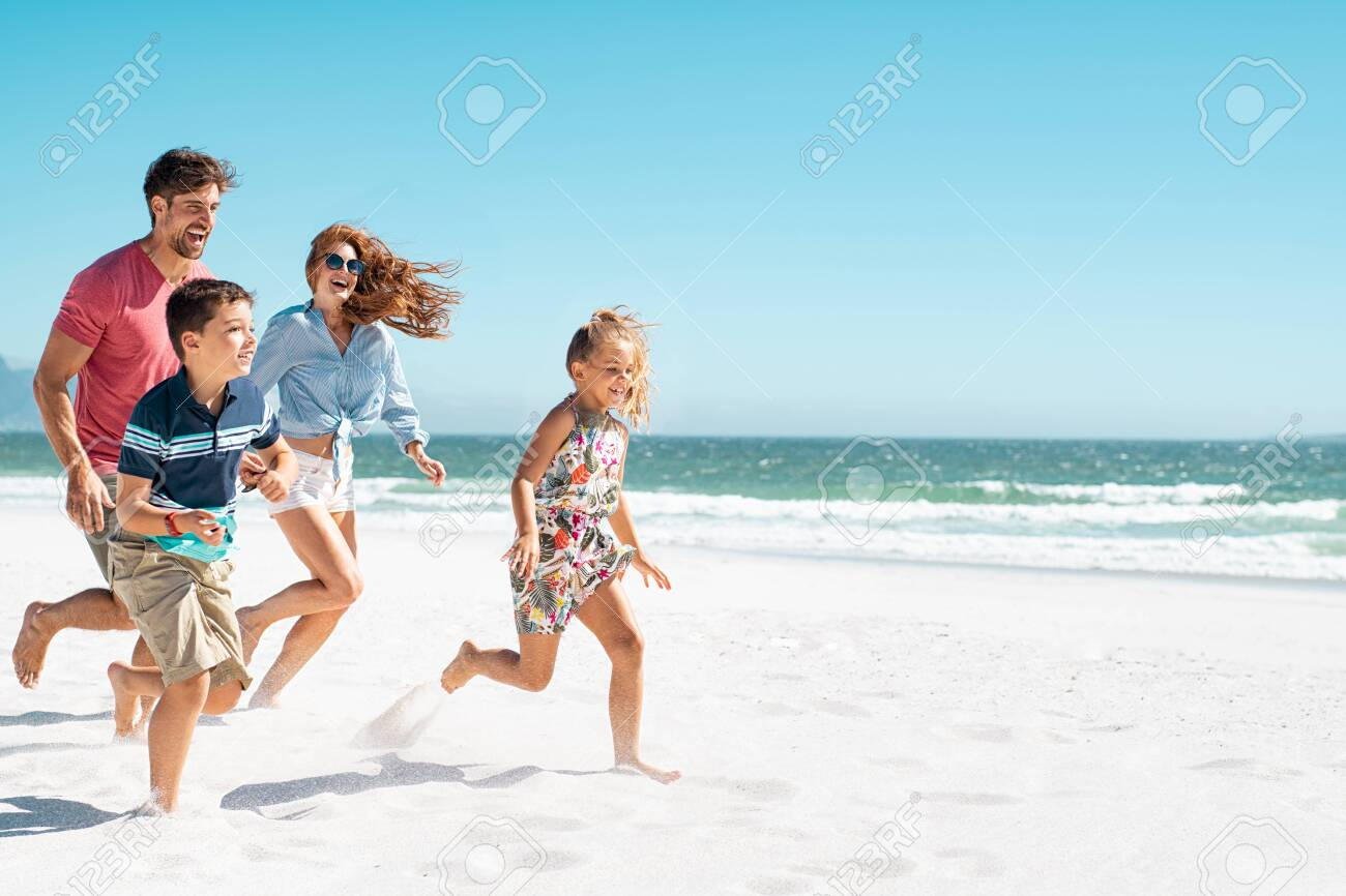 Cheerful young family running on the beach with copy space. Happy mother and smiling father with two children, son and daughter, having fun during summer holiday. Playful casual family enjoying playing at beach during vacaton. - 121442084