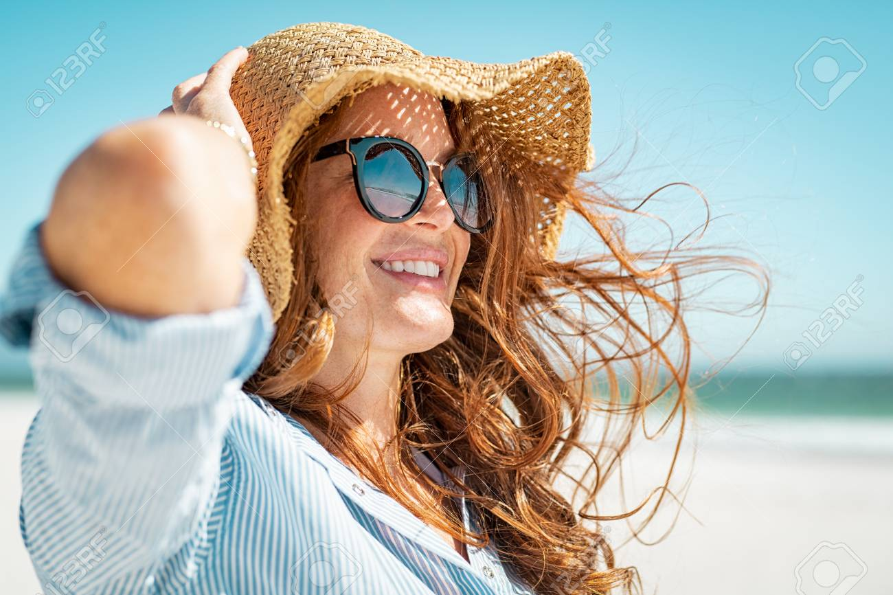 Side view of beautiful mature woman wearing sunglasses enjoying at beach. Young smiling woman on vacation looking away while enjoying sea breeze wearing straw hat. Closeup portrait of attractive girl relaxing at sea. - 121442089