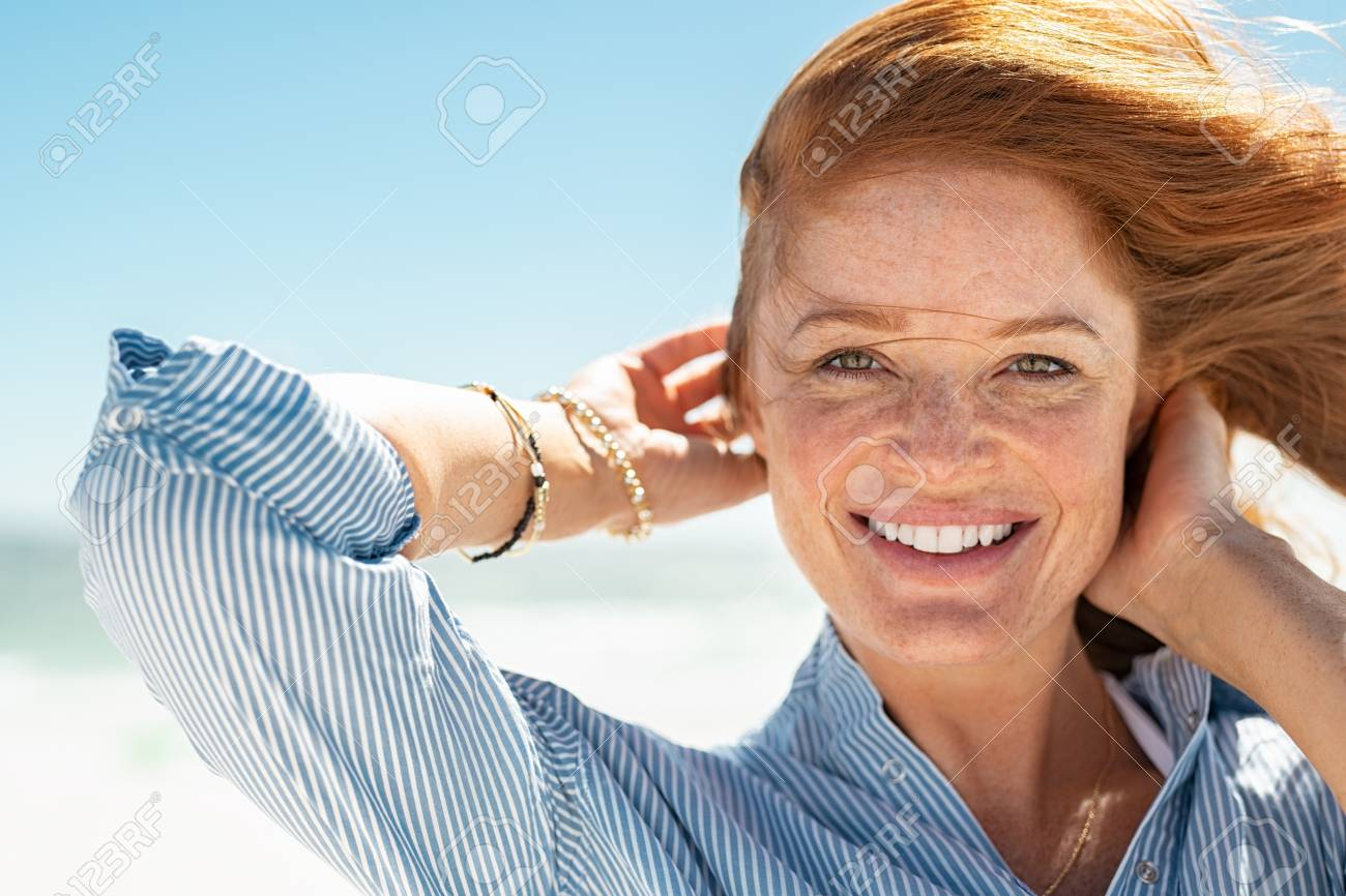 Portrait of beautiful mature woman with wind fluttering hair. Closeup face of healthy young woman with freckles relaxing at beach. Cheerful lady with red hair and blue blouse standing at seaside enjoying breeze looking at camera. - 121442126