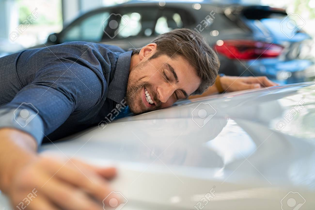 Happy young man hugging his new car in showroom. Satisfied guy with closed eyes embracing the hood of the automobile. Dreaming man lying on car bonnet hugging it. - 121442233