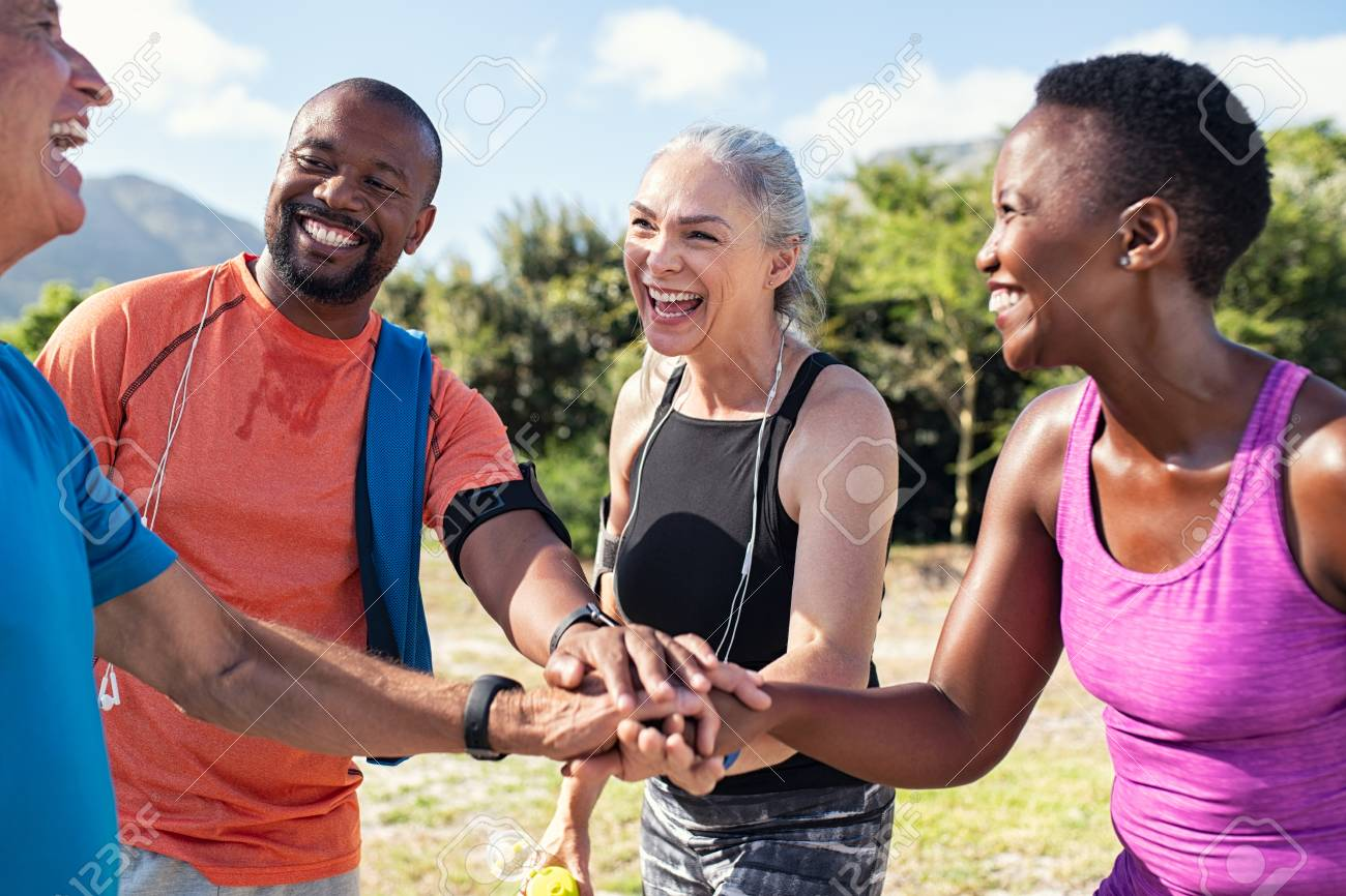 Laughing senior and multiethnic sports people putting hands together at park. Happy group of men and women smiling and stacking hands outdoor. Multiethnic sweaty team cheering after intense training. - 124982765