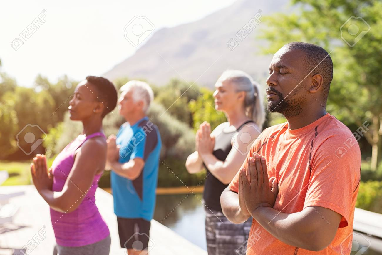 Four senior people meditating with joined hands and closed eyes breath deeply. Multiethnic group doing breathing exercise during yoga session outdoor. Class of mature people doing meditation with joined hands and relaxing together at park. - 124982943