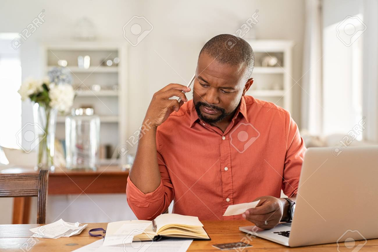 Mature man paying bills with laptop while talking on phone. Thoughtful man at home in conversation over smartphone while checking receipts. Worried african man discussing expenses over phone with bank insurance. - 124983091