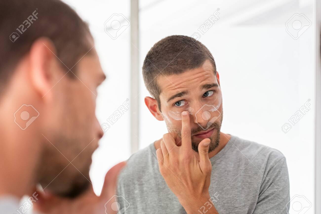Young man taking care of his undereye wrinkles putting anti aging eye moisturizer. Man applying skincare facial treatment cream on face in the bathroom. Handsome guy applying moisturizer and looking at himself while standing in front of the mirror. - 127284792