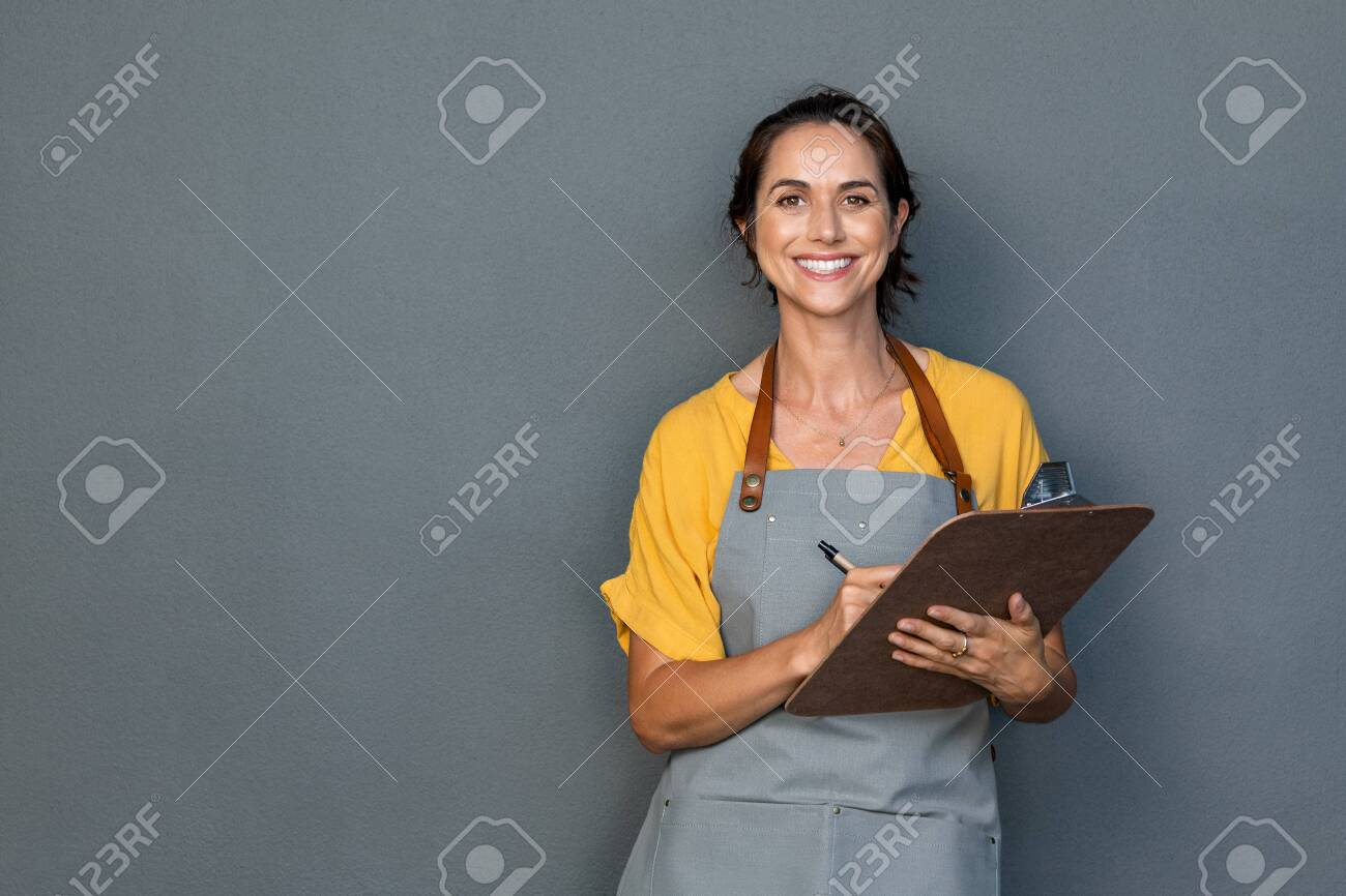 Happy smiling waitress taking orders isolated on grey wall. Mature woman wearing apron while writing on clipboard standing against gray background with copy space. Cheerful owner ready to take customer order while looking at camera. Small business concept. - 132031233