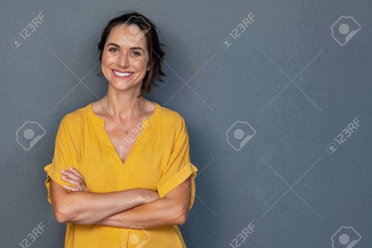 Confident mature woman with crossed arms in casual clothing standing against grey background with copy space. Successful smiling woman with toothy smile looking at camera. Beautiful positive businesswoman standing. - 131556621