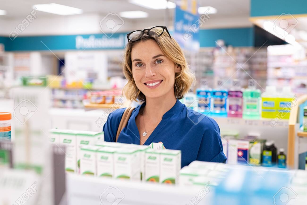 Portrait of smiling woman choosing dietary supplement at pharmacy in shopping mall. Happy mature woman customer buying lotion in skincare section of chemist's. Woman checking medicine and drugs in shelf at drugstore while looking at camera. - 148898353