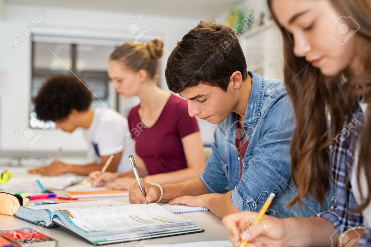 Group of college students studying in classroom writing notes during lesson. Focused guy and girls studying in college library sitting at desk. Group of multiethnic university students doing research sitting in a row. - 156811208