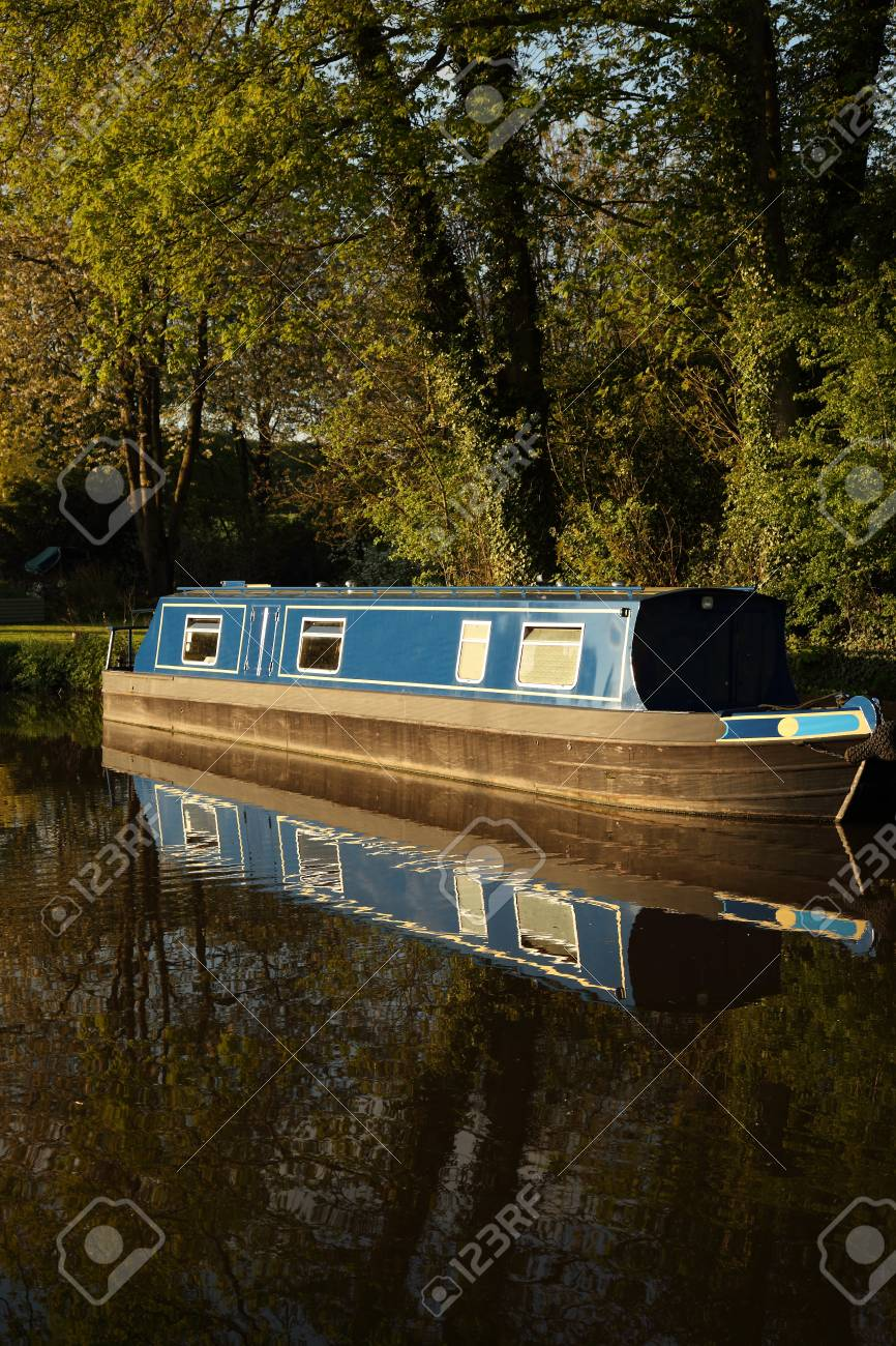 Canal barge narrow boat reflected in water surrounded by trees