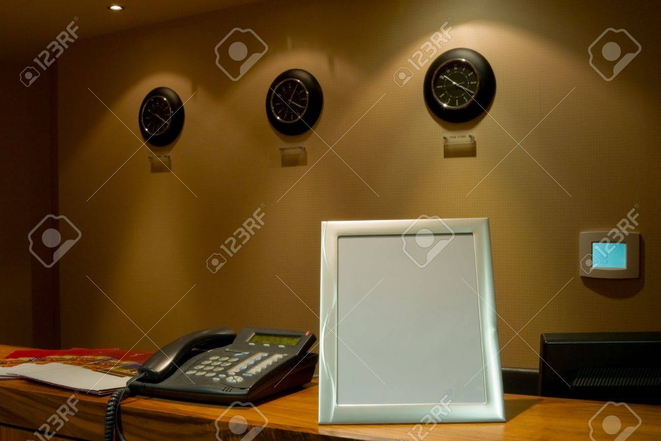 hotel reception desk with phone and row of clock on the wall Stock Photo - 8363451