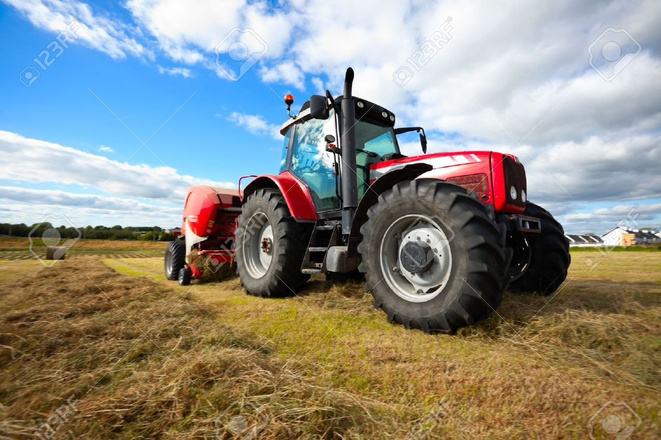 huge tractor collecting haystack in the field in a nice blue sunny day Stock Photo - 10101623
