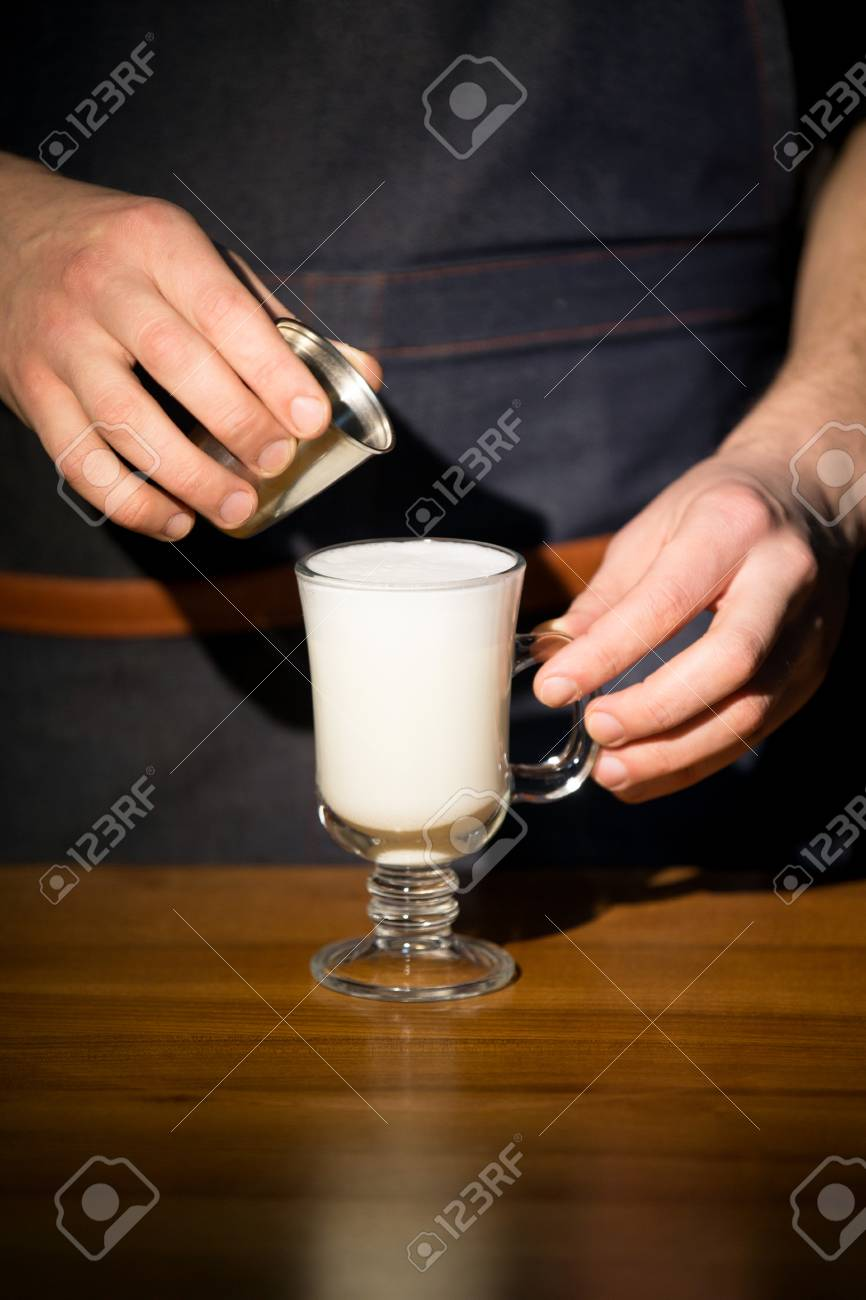 Hand on the barista, making a latte cafe, a cup of coffee with a beautiful latte - 99735860