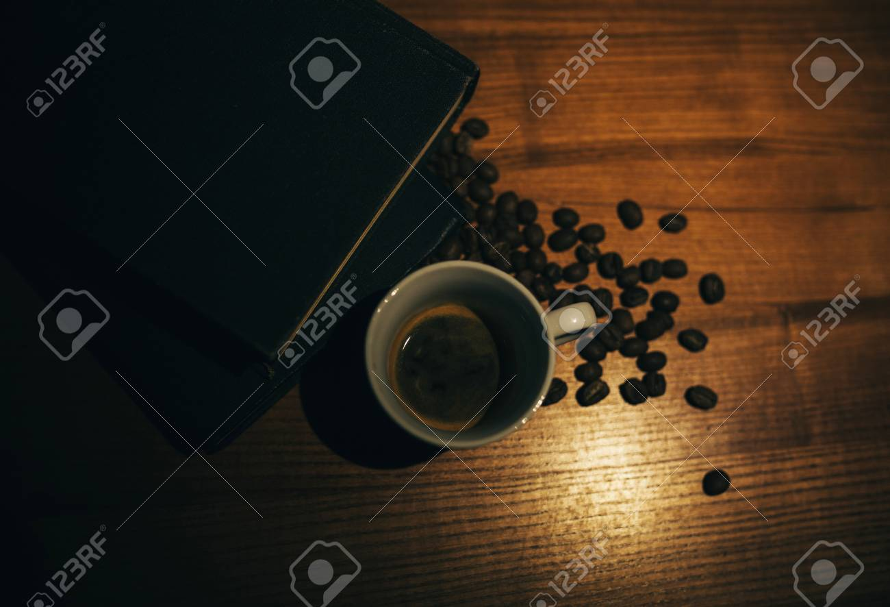 A cup of black coffee and coffee beans and a book on a wooden table. top view. - 99739777